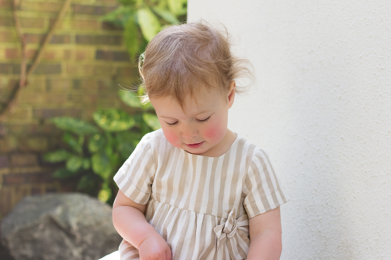 The birthday girl looks down in a pretty cream and white striped dress