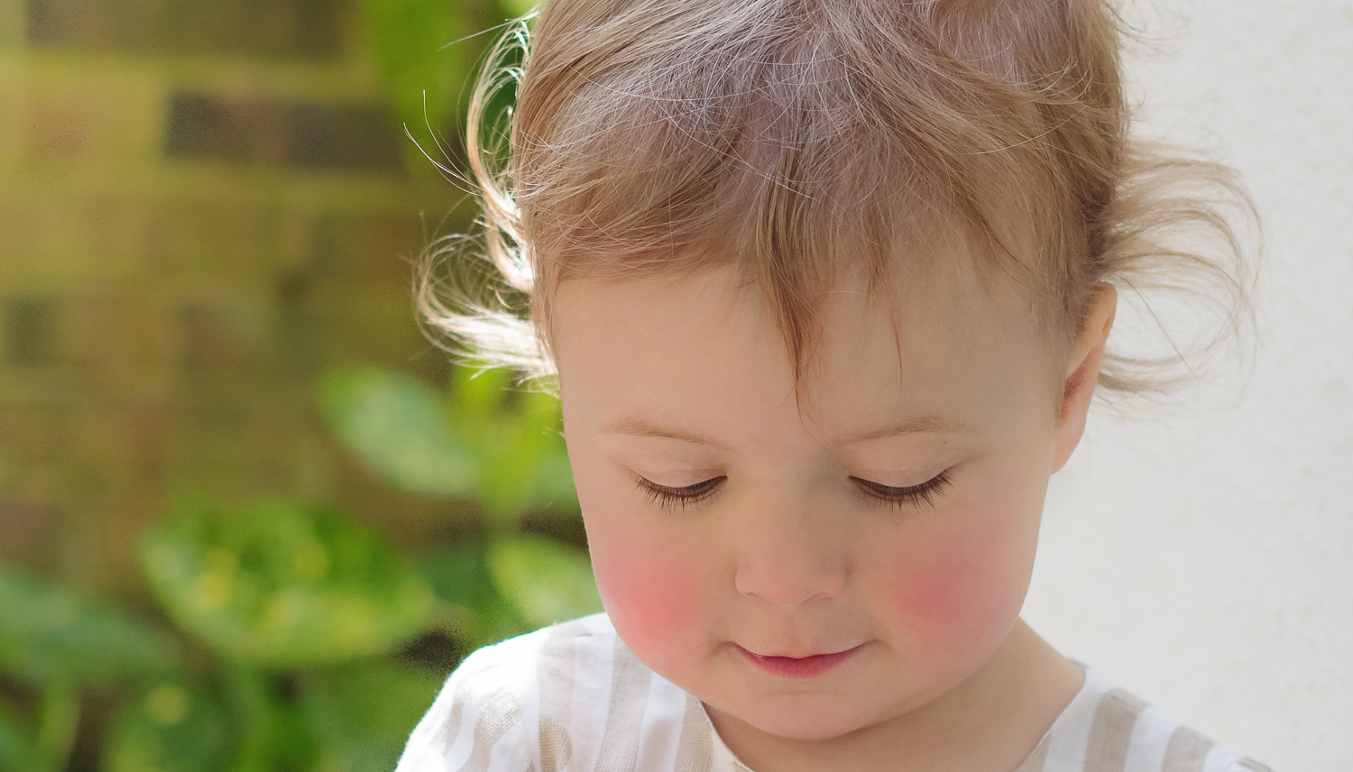Professional children's party photography - a close up of the birthday girl, showing the little curls in her hair and her rosy cheeks