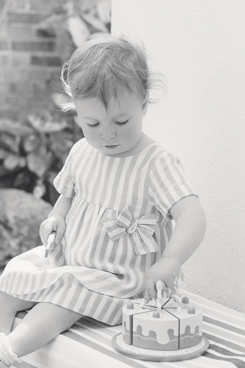 Black and white fine art image of a little girls second birthday party - she sits on her own playing with her pretend wooden cake and candles
