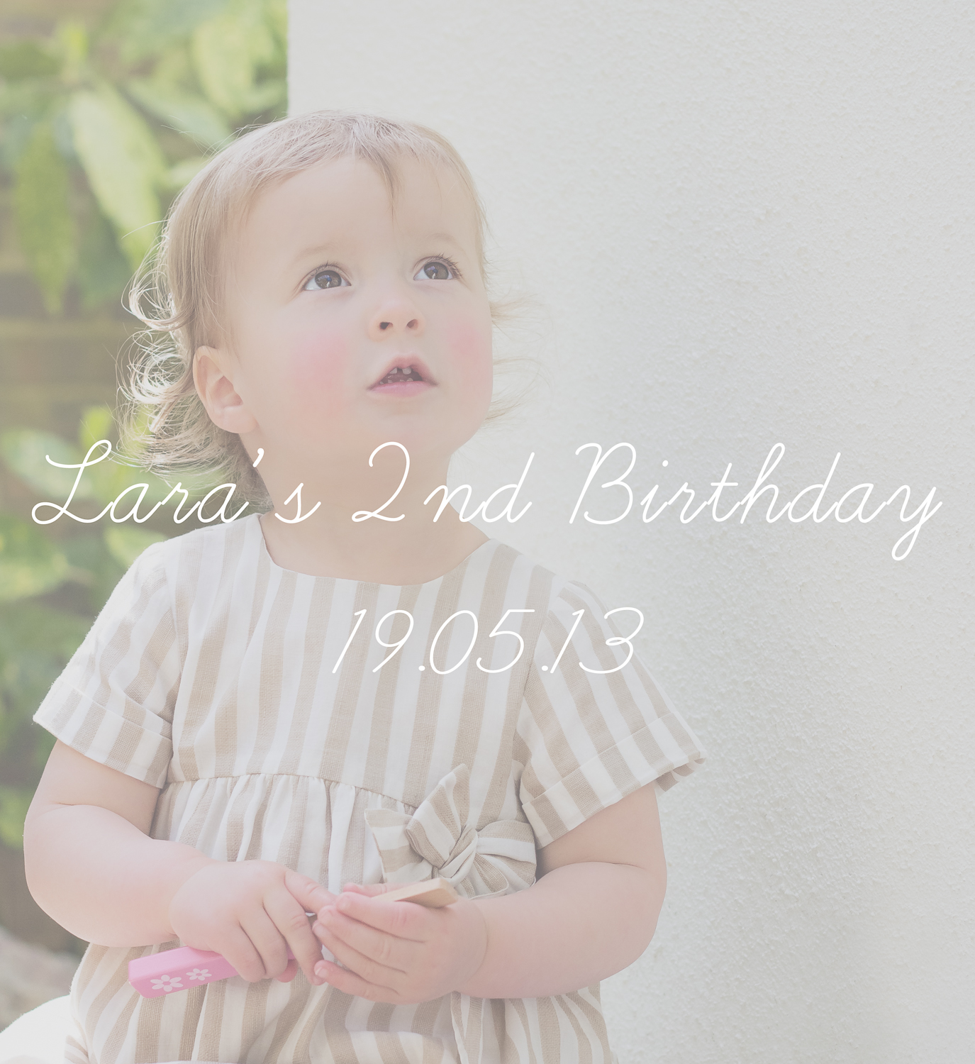 Girl's 2nd Birthday party photography - the birthday girl is sitting down and looking up, she is wearing a cream and white striped party frock