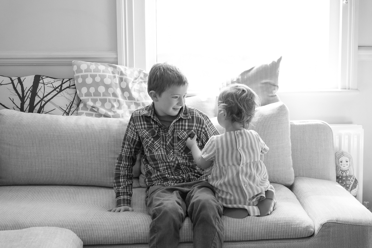 Two children sit on a sofa in the lounge playing with eachother