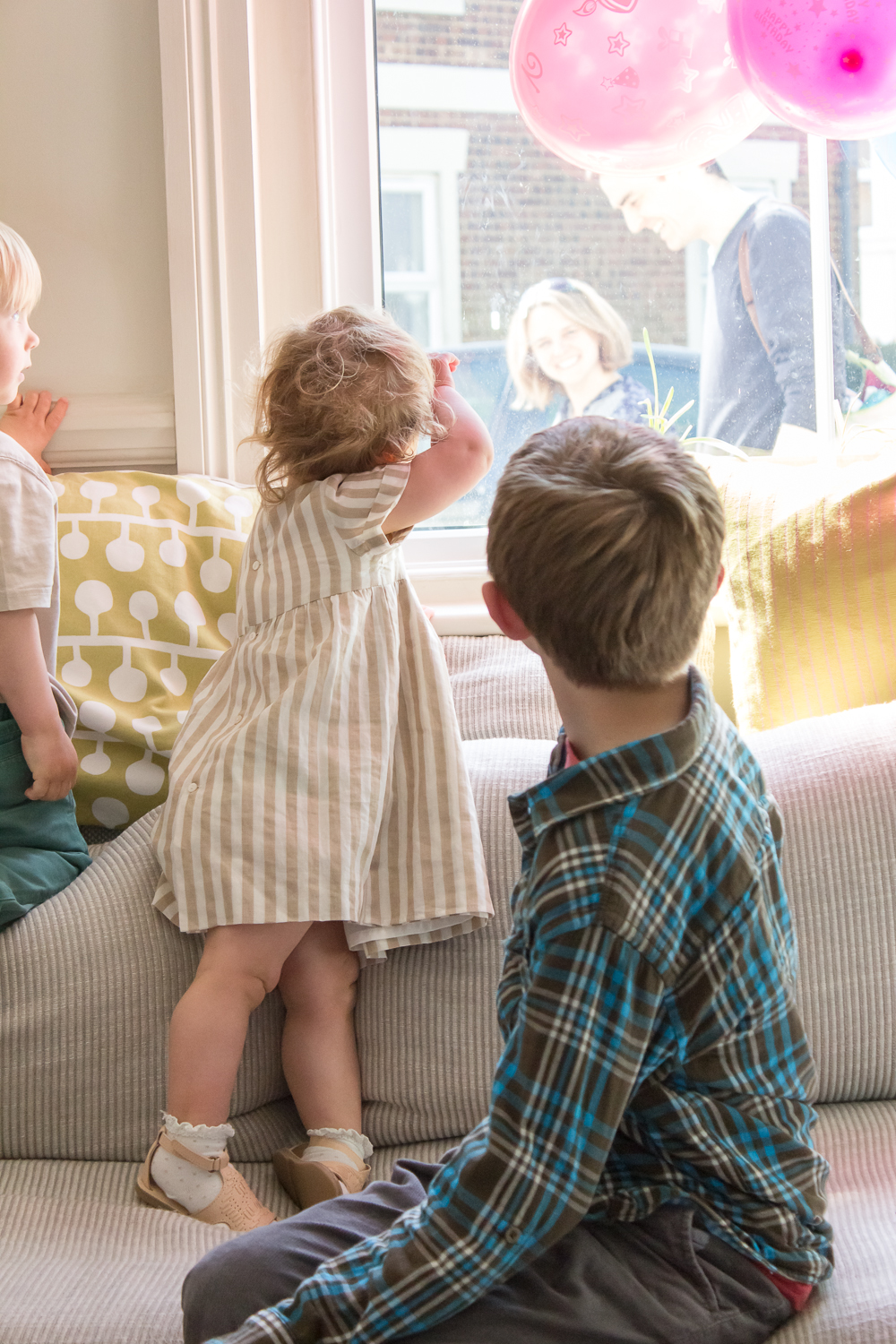 An indoor photograph of a child's birthday party - two children look out the window as guests arrive to the party