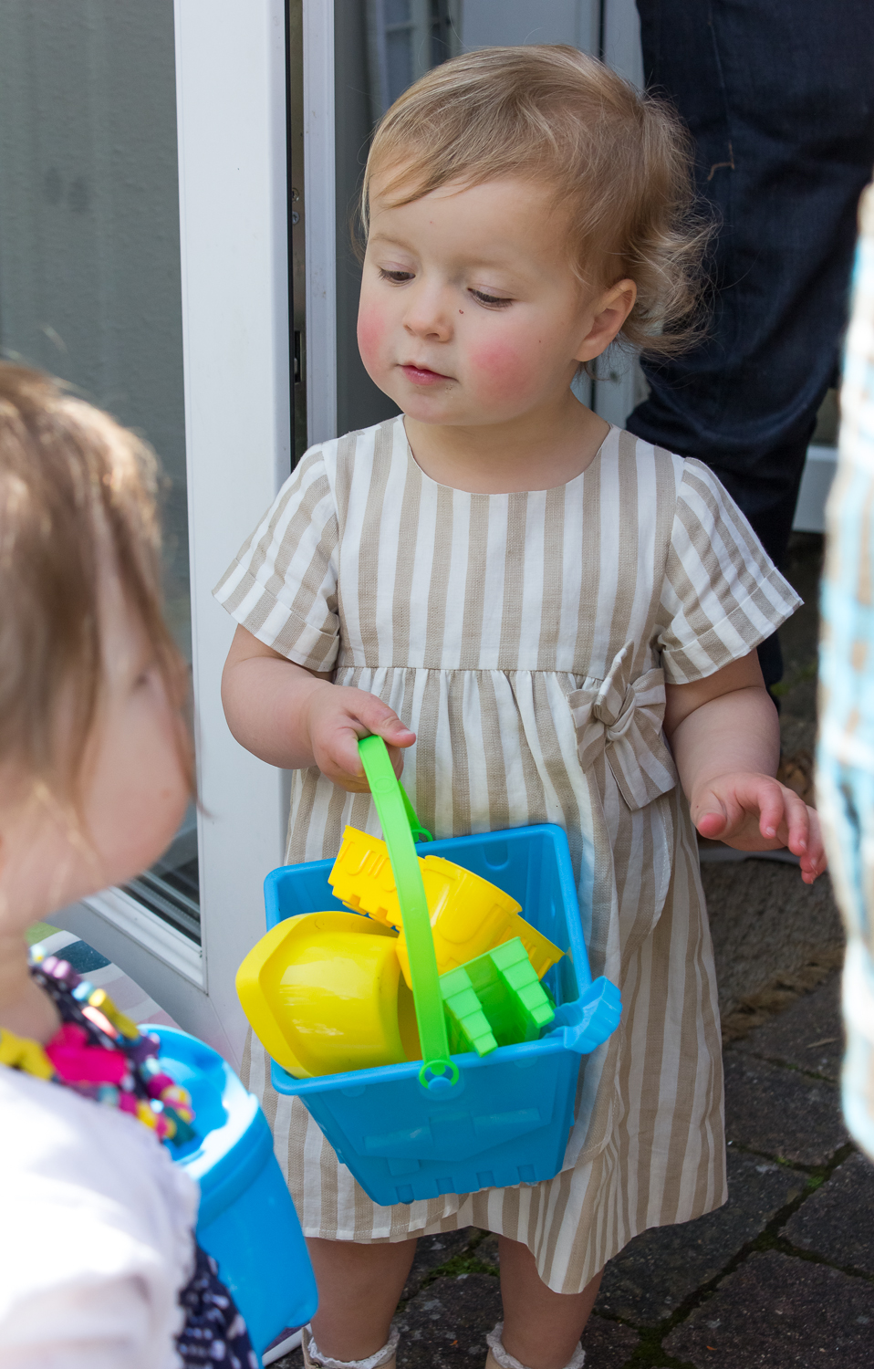 A professional birthday photograph showing the birthday girl playing with her bucket and spade, collecting items in her bucket from around the garden