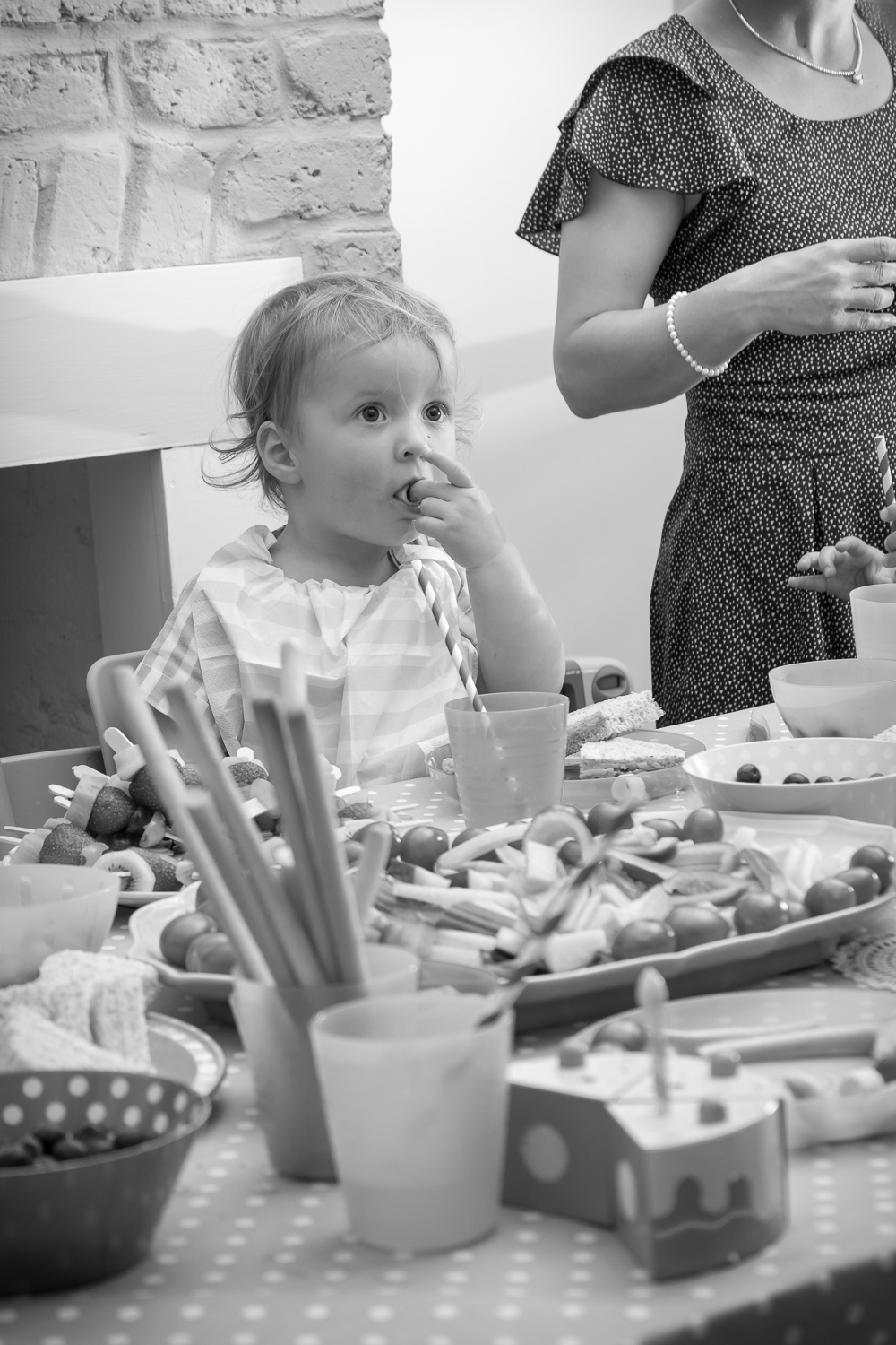 A two-year-old at her birthday party eating her birthday lunch