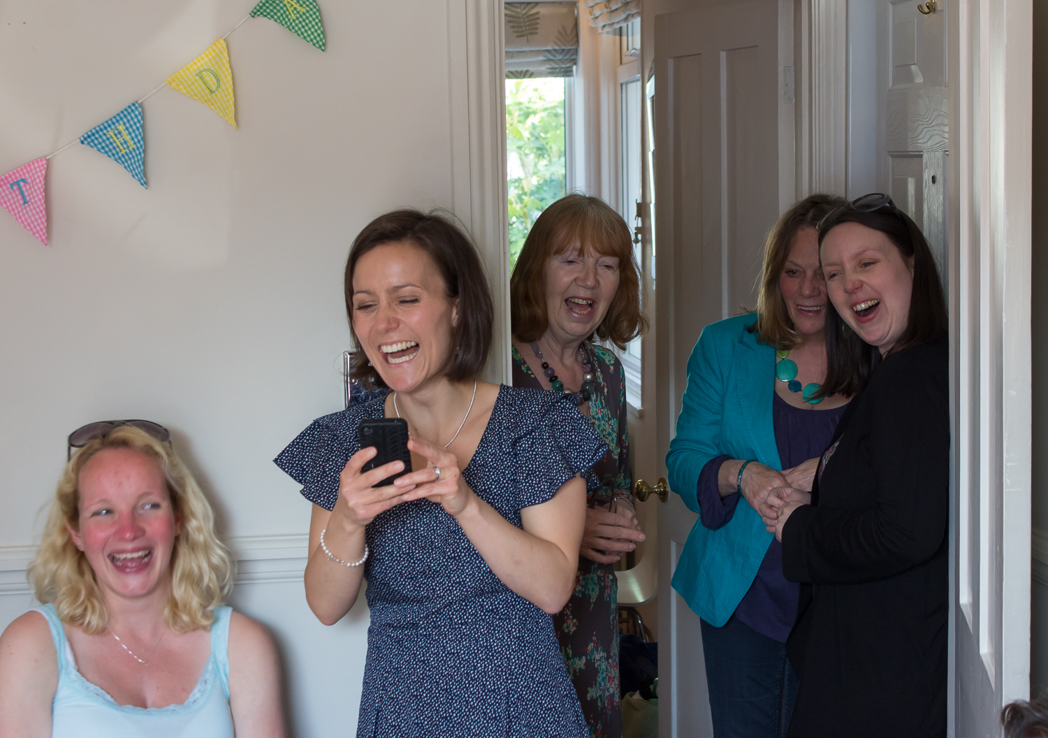 Family members crowd around the lounge door at a girls second birthday party, laughing away