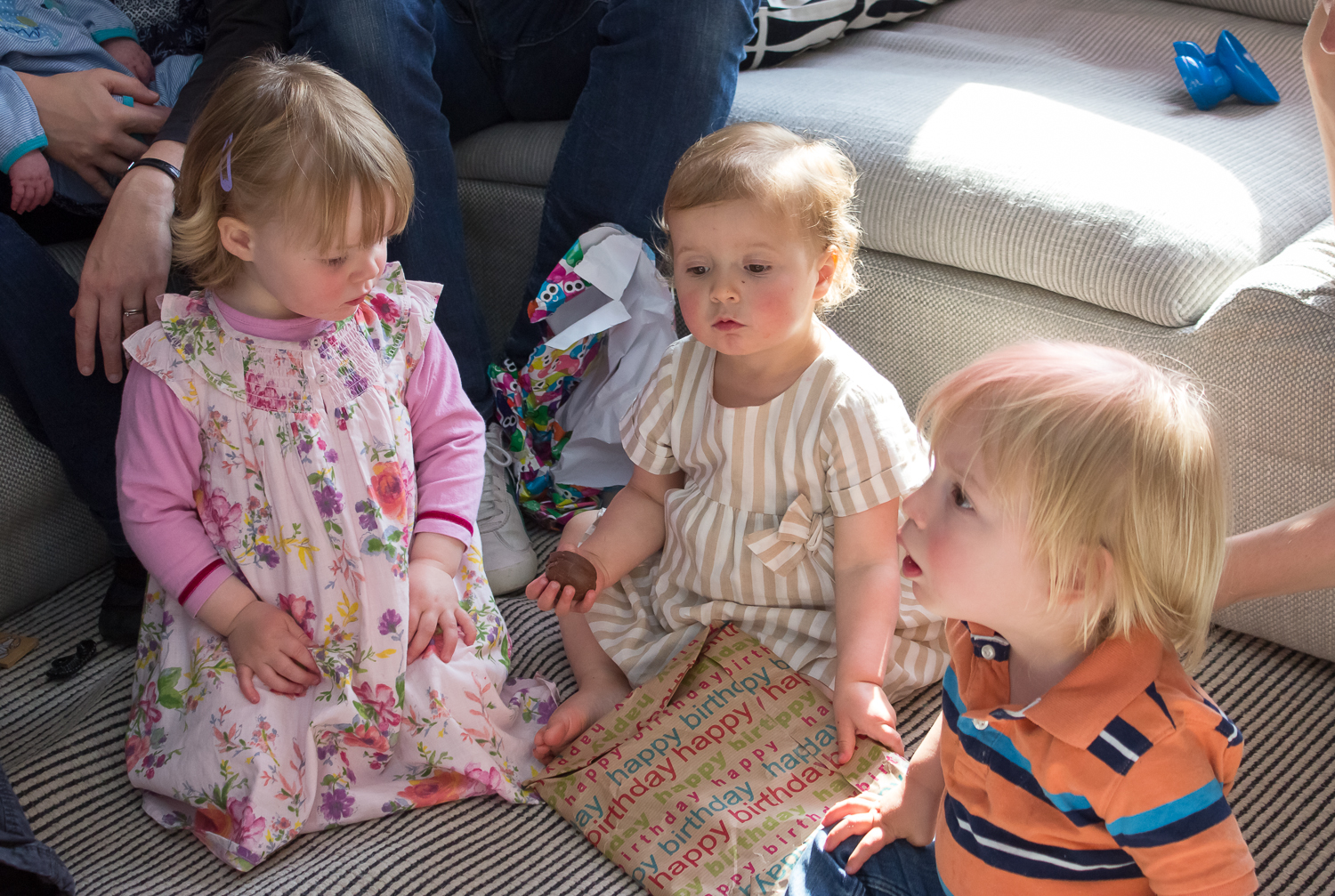 Three children sat on a lounge floor playing parce-the-parcel, clucthing their winnings