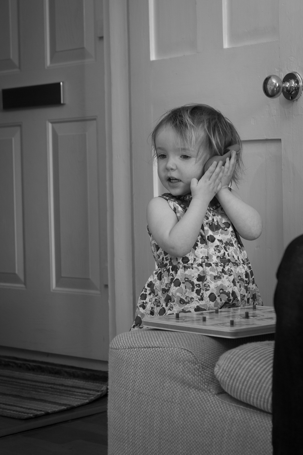 A fine art black and white image of a little girl using a toy phone - she looks with intent as if somepone is really on the other end talking to her