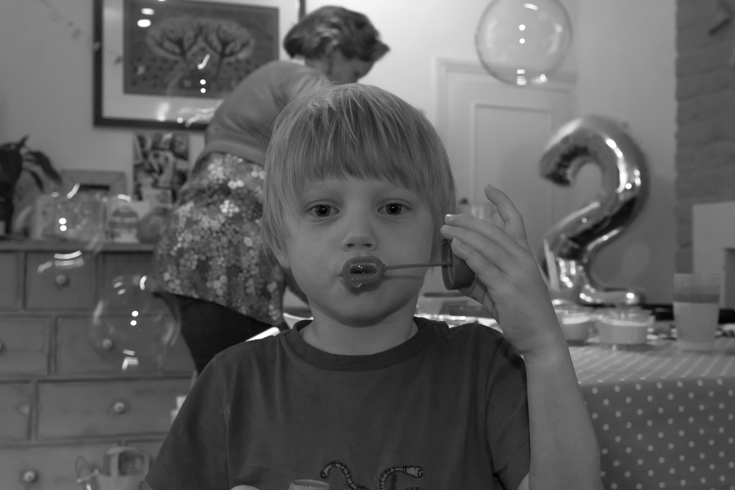 A young boy blows bubbles at the camer, while a grandmother tidies up after the party in the background
