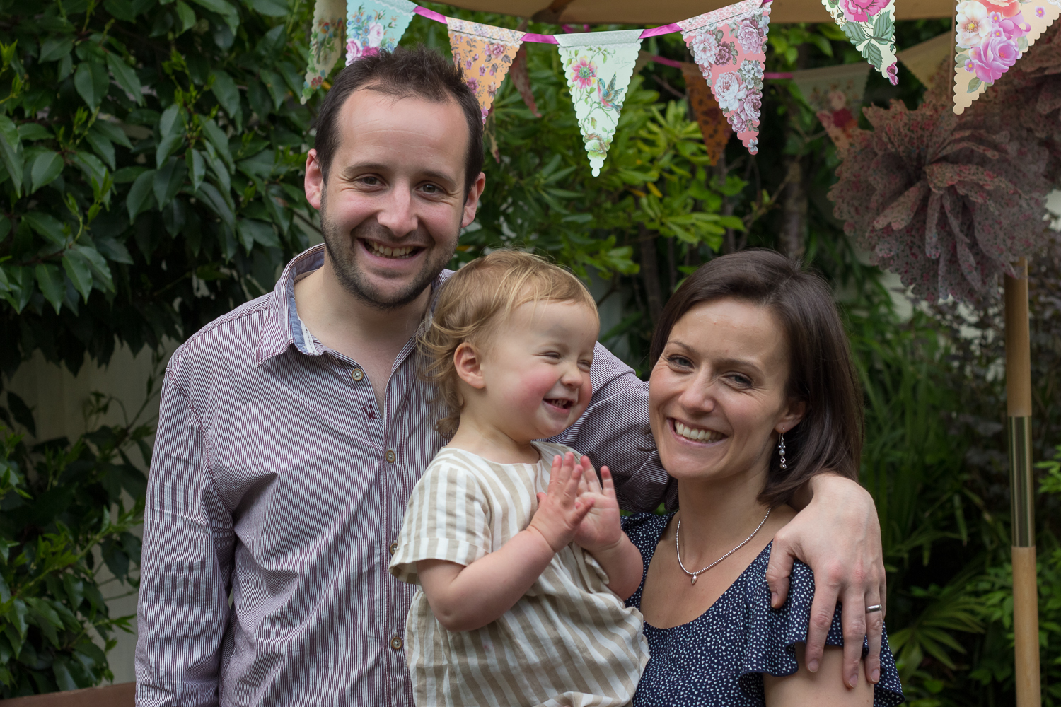 A mum, dad and their birthday girl pose for a family photograph in their garden in Tunbridge Wells - the little girl is clapping her hands, and you can see bunting in the background