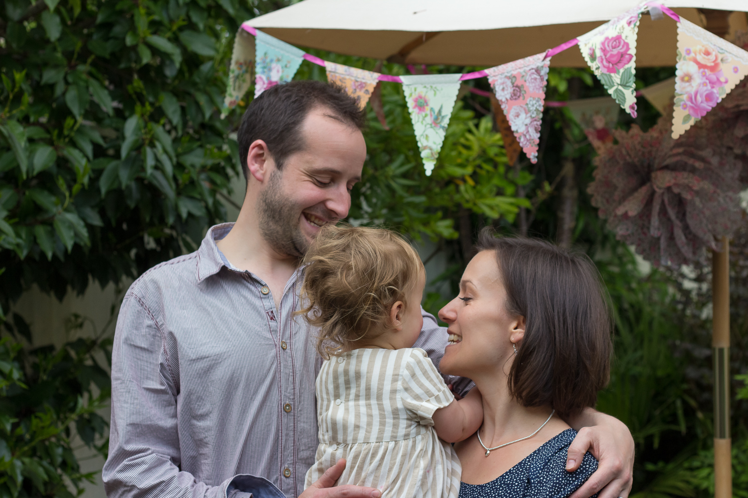A mum, dad and their birthday girl pose for a family photograph in their garden in Tunbridge Wells