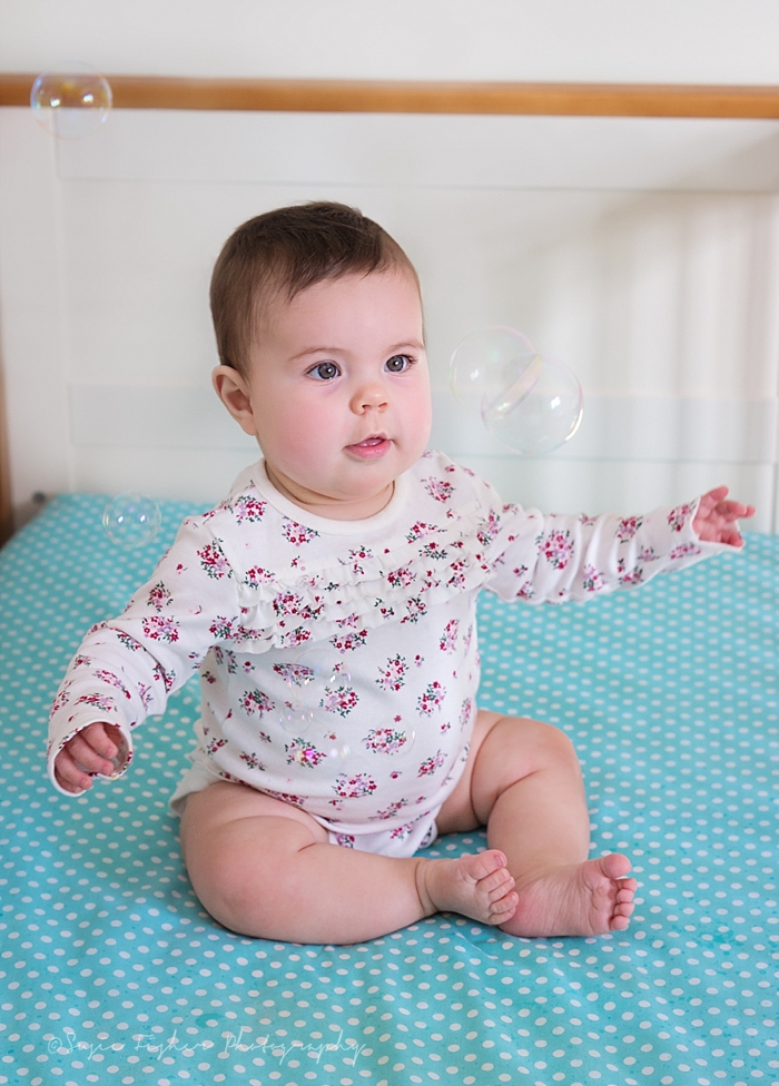 Baby girl playing with bubbles in her crib.jpg