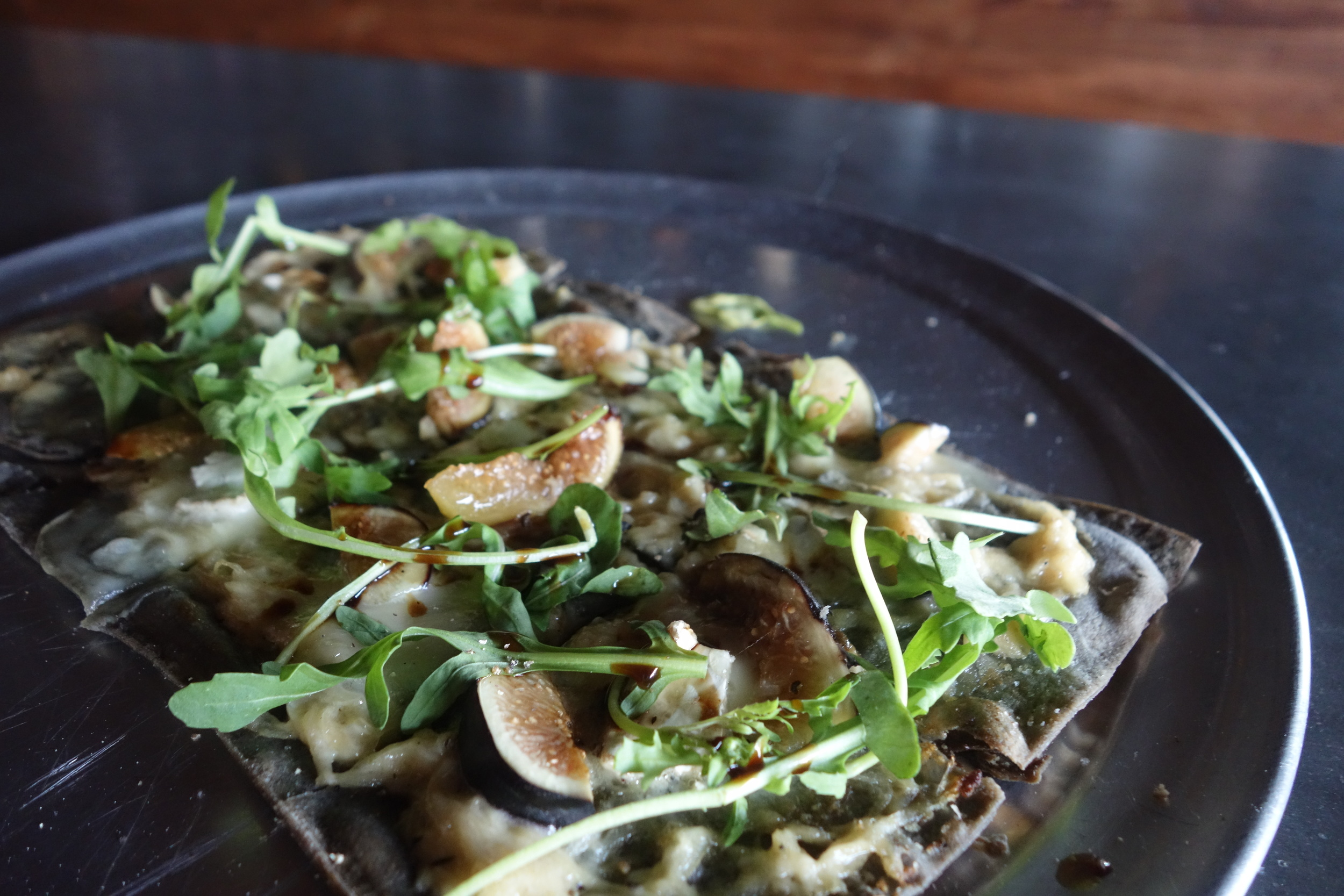 Even if you go for the pies (duh!), go for the tartes too. This one has caramelized onion and Brie on a flaky, light-as-air bread infused with squid ink, and topped with fresh figs, arugula and balsamic vinegar. (Photo by Nicole Reed)