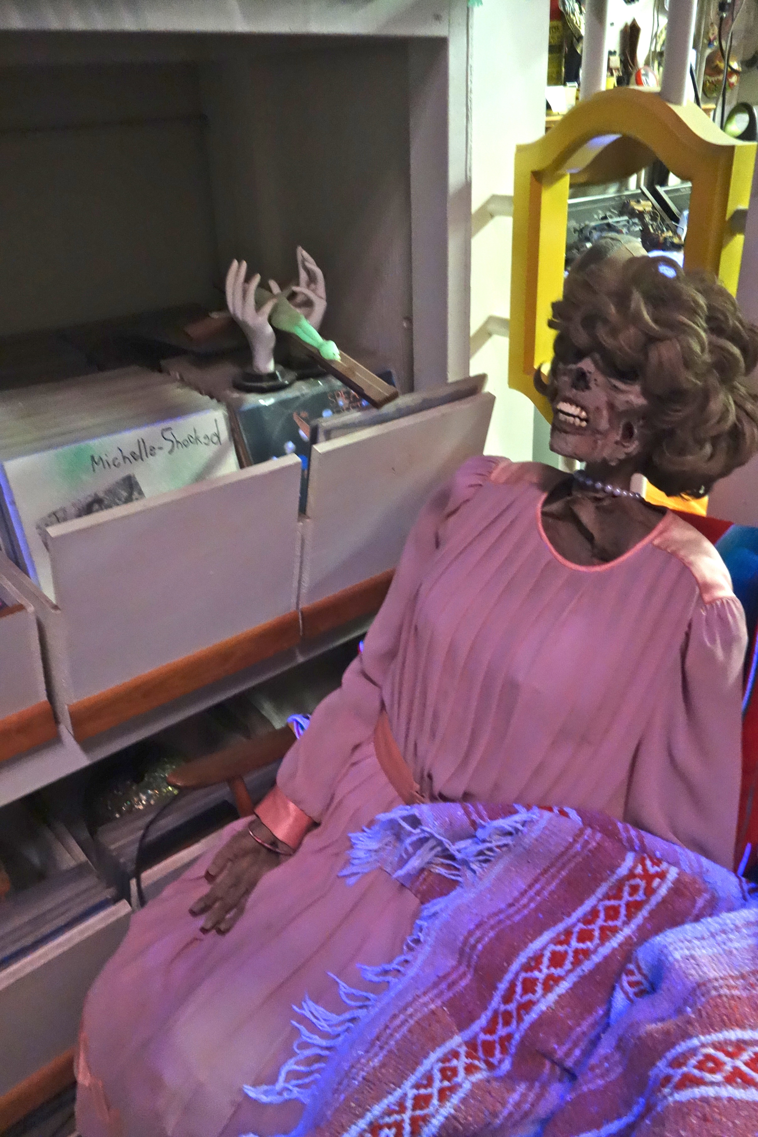 A zombie lady in a pink dress and pearls snuggles up on the sofa next to Rose impressive vinyl collection.