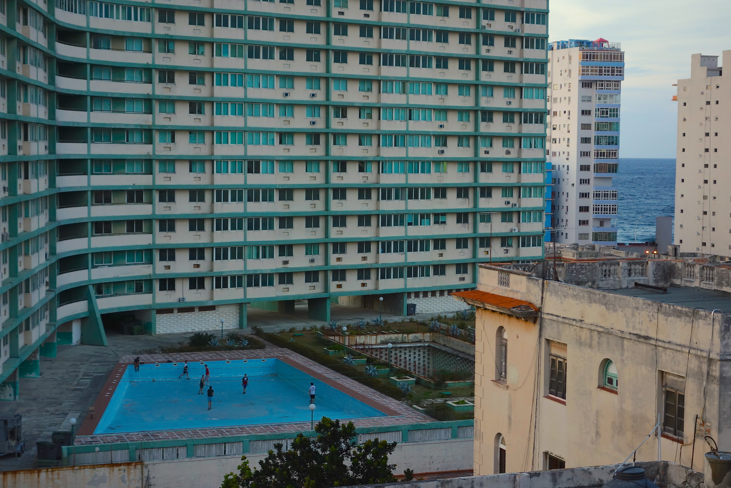 Our view from Cafe Laurent: Kids play soccer in the empty pool of the Riviera Havana, a ghost of the mid-century glamour that once defined Havana.
