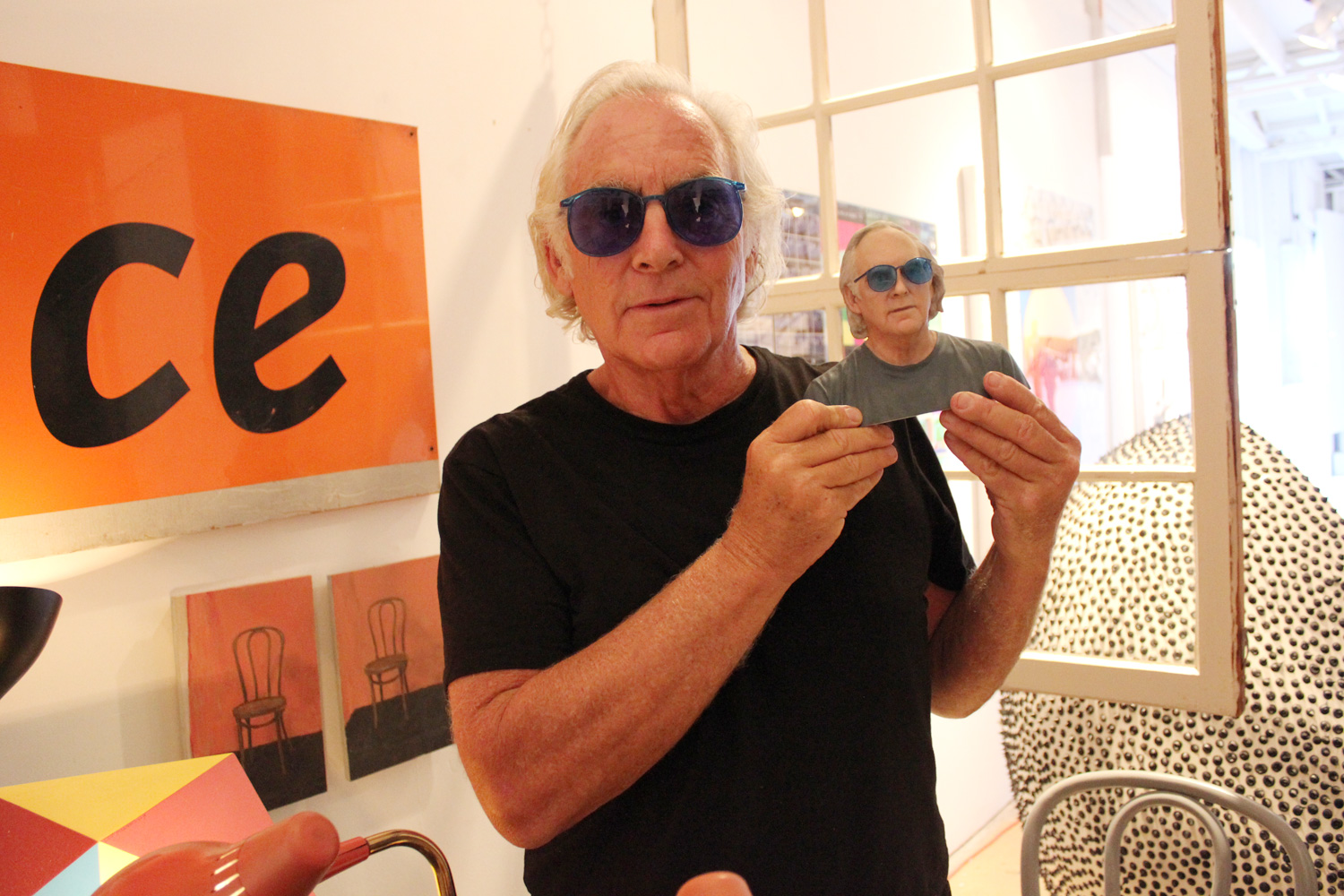 """Budman says that his blue sunglasses are a statement of high-low design. """"The sunglasses are inexpensive,"""" he says. """"Sometimes I give them away."""" He likes the way they look and likes to see the world in his favorite color."""