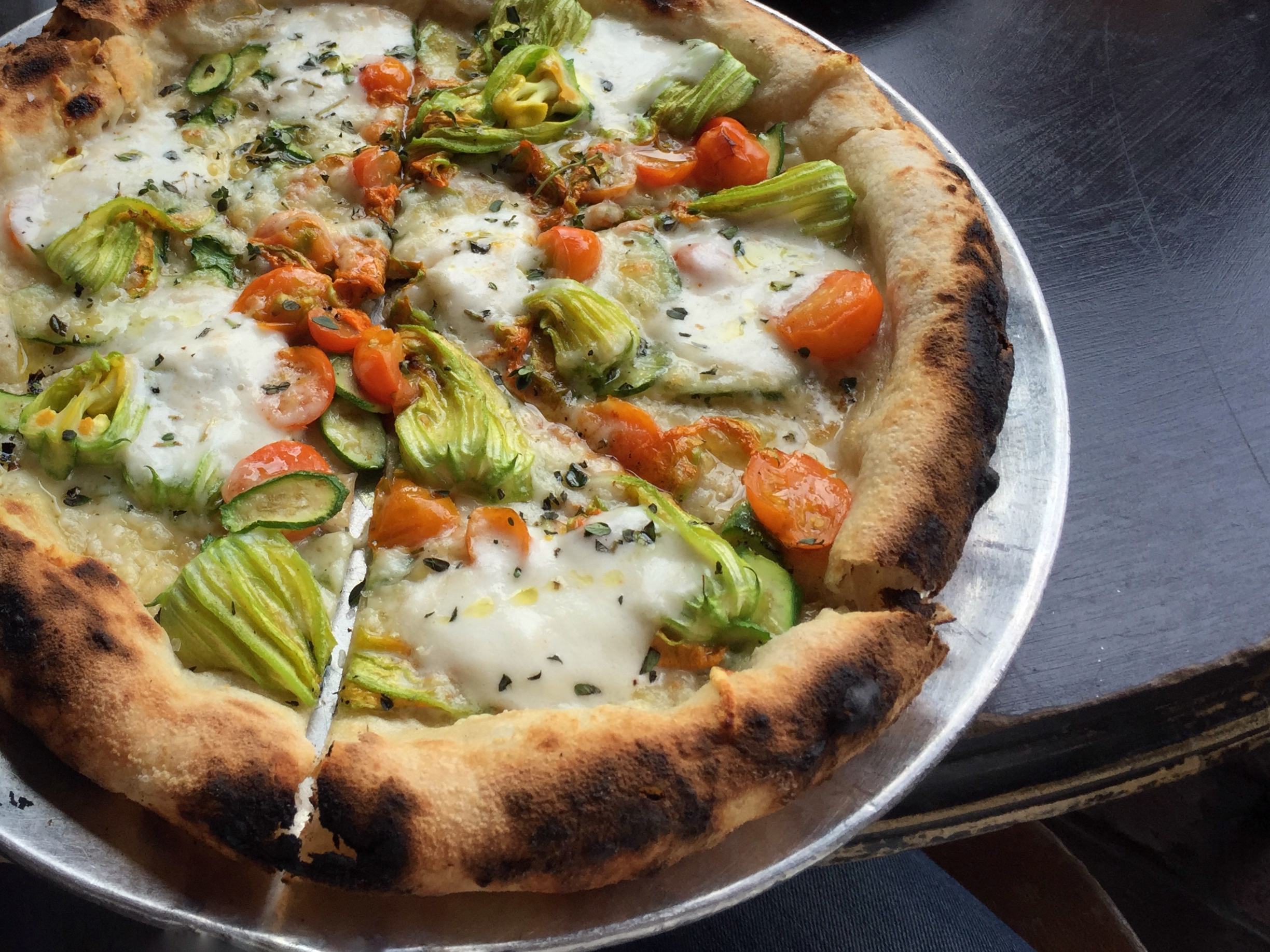 Gjelina's squash blossom pizza with cherry tomatoes, thyme, burrata and Parmesan. ( Photo by Lincoln & Rose )