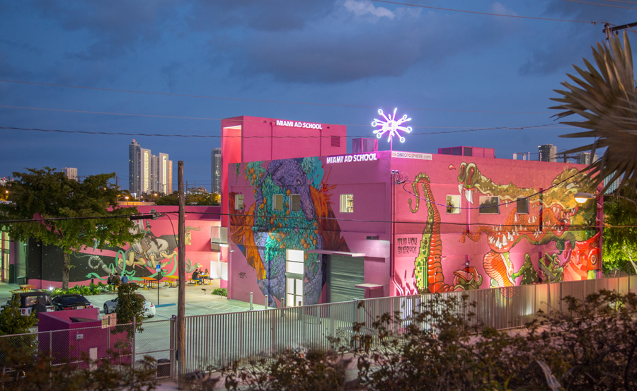 With the city skyline in the distance, this new academic campus and headquarters utilizes its entire site. The existing and new structures were given visual cohesion with a coat of bright pink paint, the school's signature color.