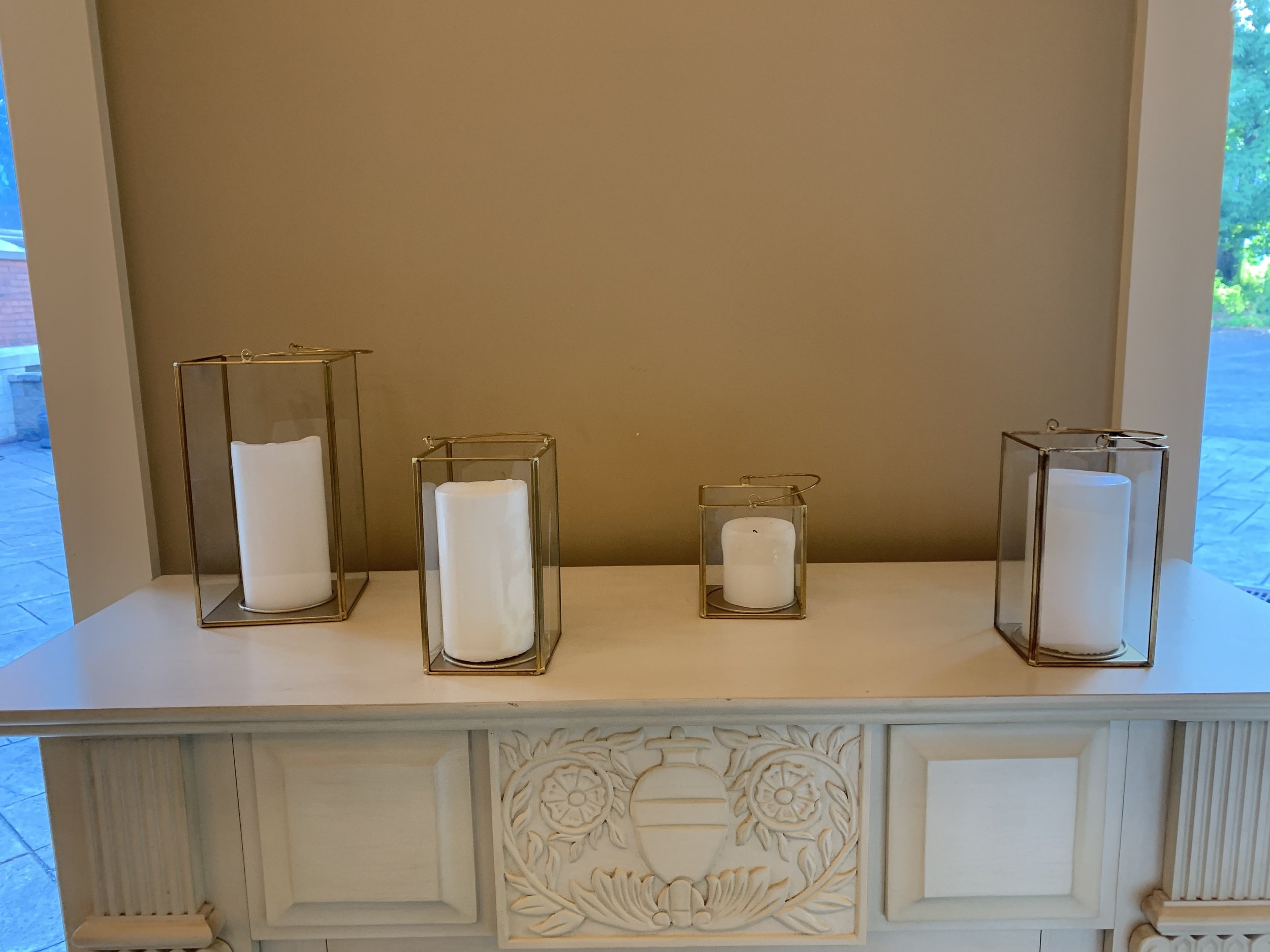 4 various-sized gold rimmed lanterns