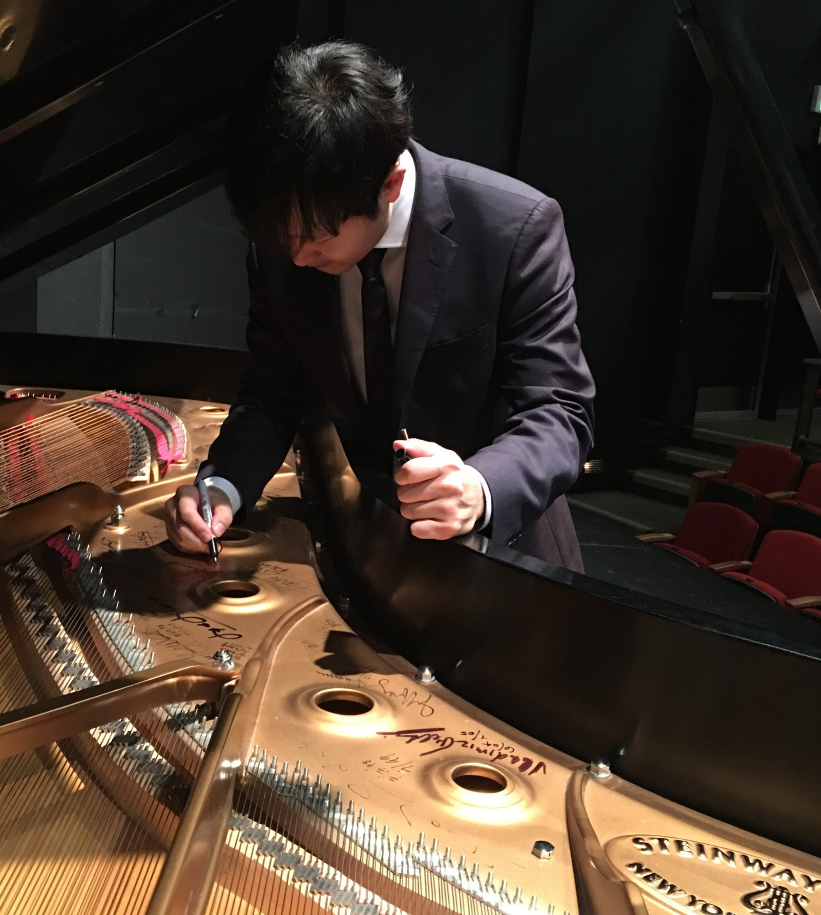 Yekwon signs the NY Steinway donated for the performance by Larry Vollum.