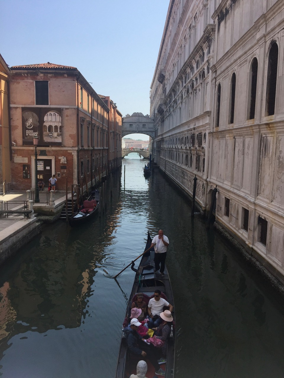 A view of a gondolier in a side canal