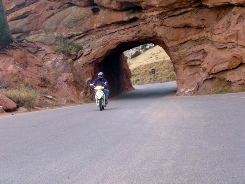 A biker ride through a rock tunnel in Morrison at Red Rocks Ampitheatre.