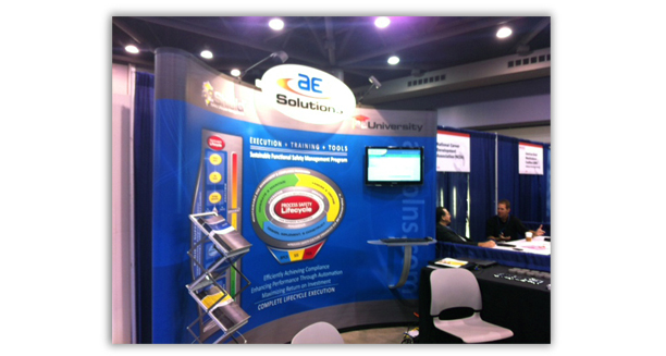 """AE Solutions booth graphic. This graphic is a whopping 20"""" x 10"""". It showcases the """"oval"""" we created for them explaining the different divisions of their business and how they work together. Notice the sleek brochure stand that shows how all of their materials go together. Also a monitor with a slide show explaining the details of their business."""