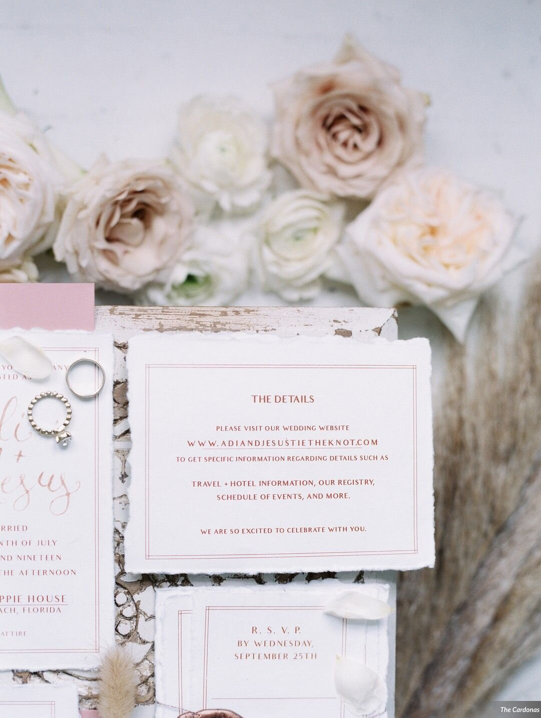 Invitation Suite printed on white handmade paper with a deckled edge or torn paper detail. Rose Gold text and spot calligraphy names and Pink/Dusty Rose Envelopes. Rose gold twine and adorned with a Rosé colored rose wax seal. Invitation suite with ring detail on a bed of rocks and foraged floral detail.