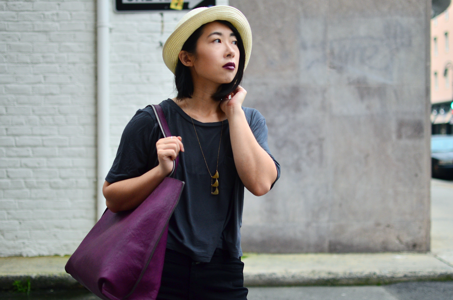 Ally looking towards the road. Wearing Aritzia fedora hat, Crafts & Love necklace, Urban Outfitters leather tote, and Gap slub tee.