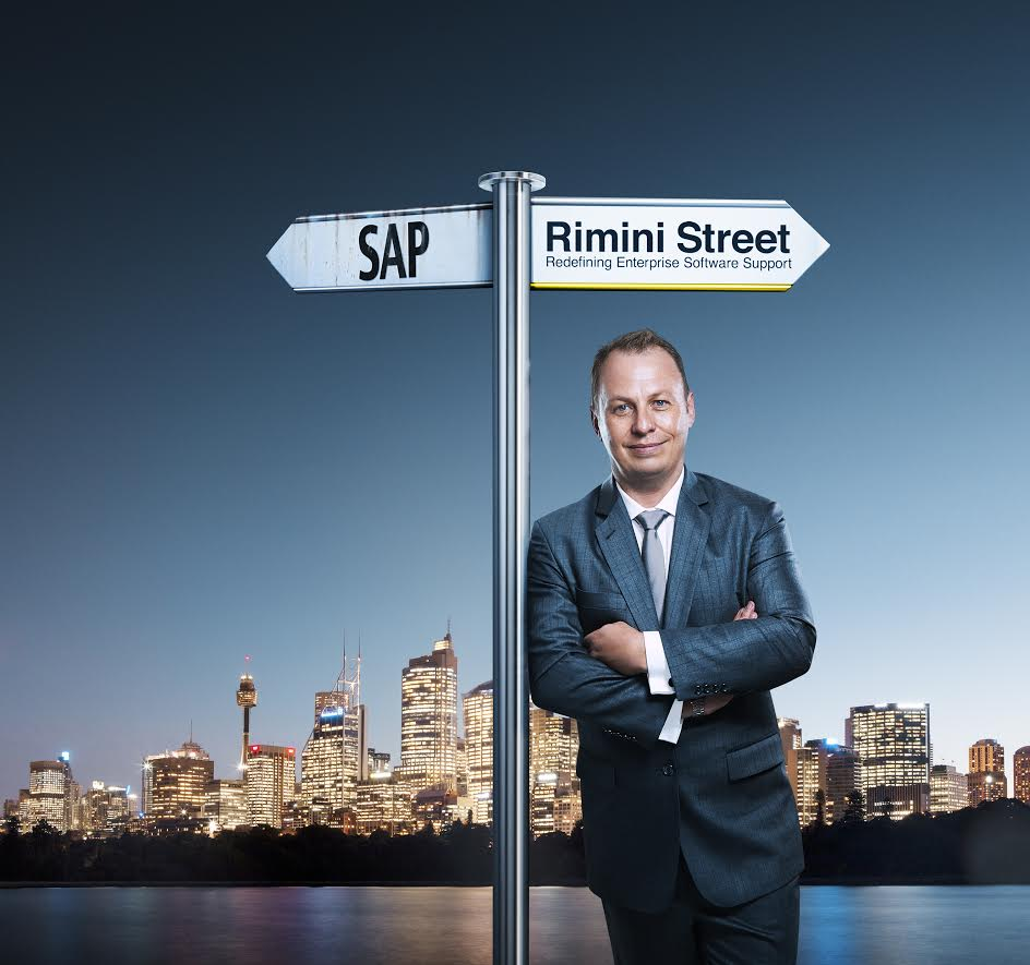 The image includes subtle details such as a weathered SAP sign while the Rimini Street sign is shiny and new. Including the corporate colours and the company tagline.  The image of Sydney in the background reinforces the local presence of Rimini Street in Australia