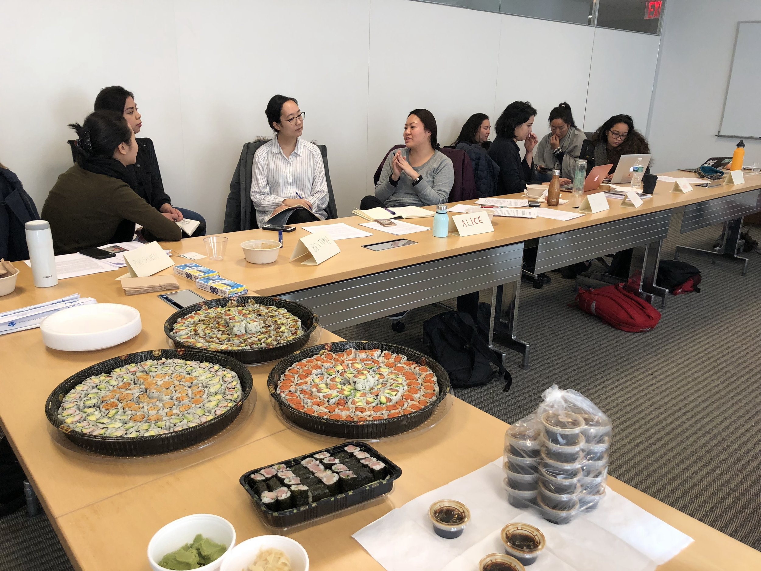 Sushi arrives while everyone breaks into groups to discuss each other's works.