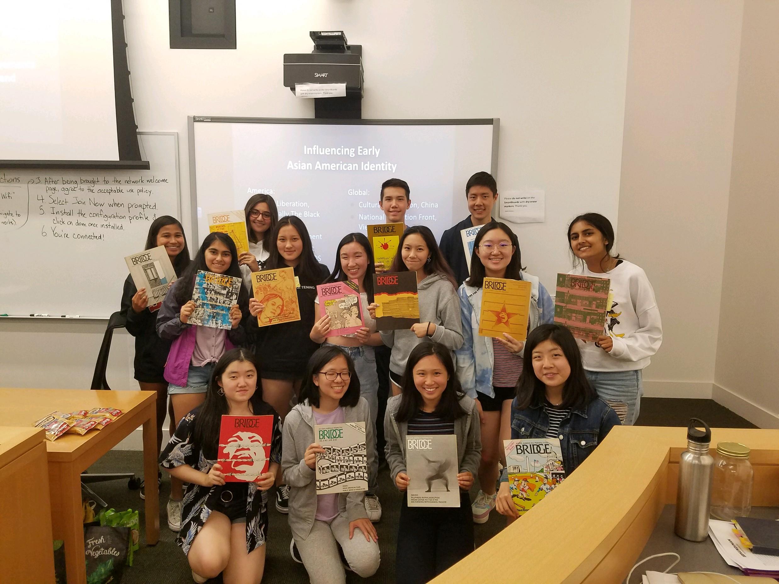 Students pose with archival copies of Bridge Magazine.