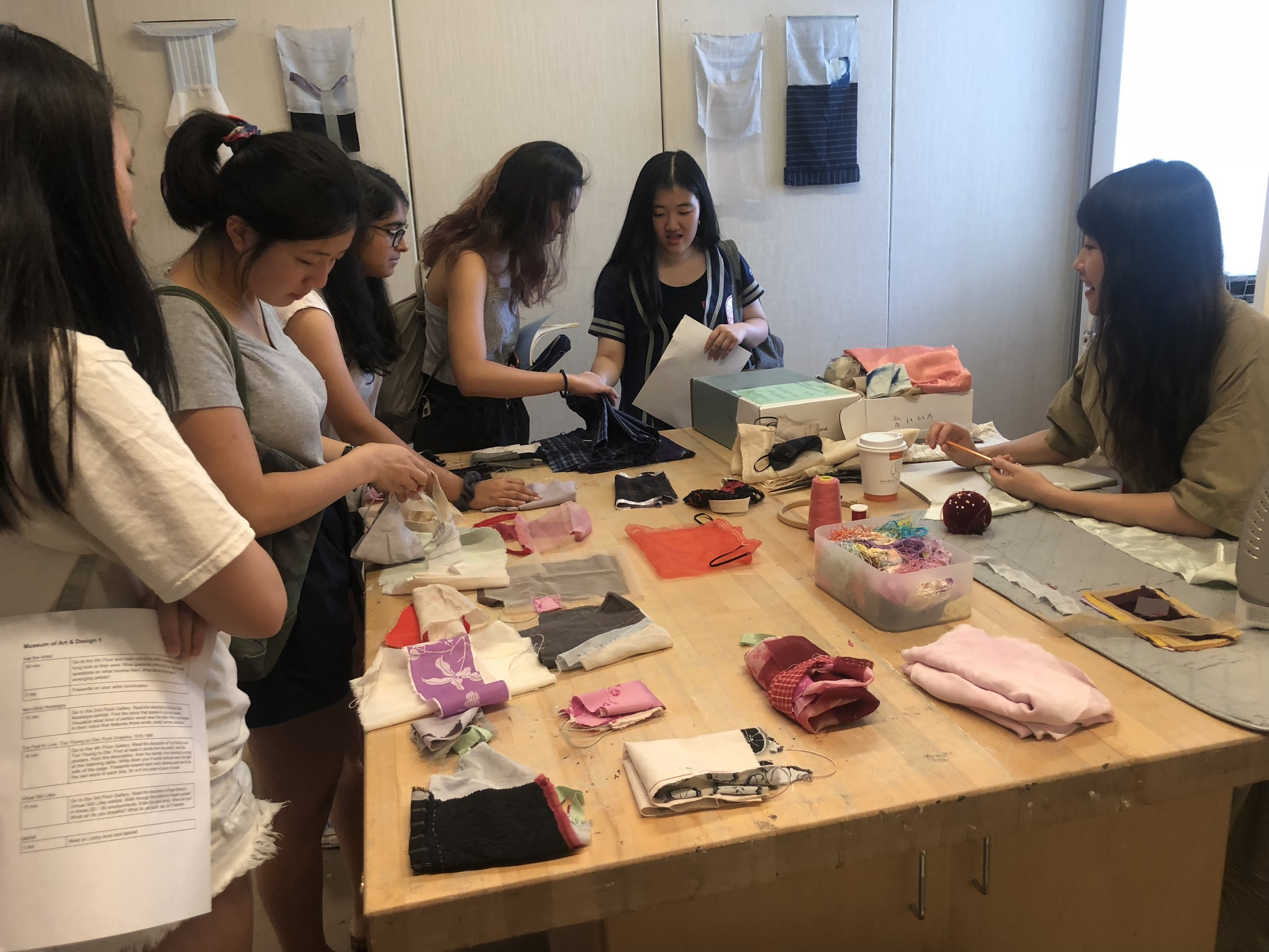 Students examine the textiles Yuchen works with.