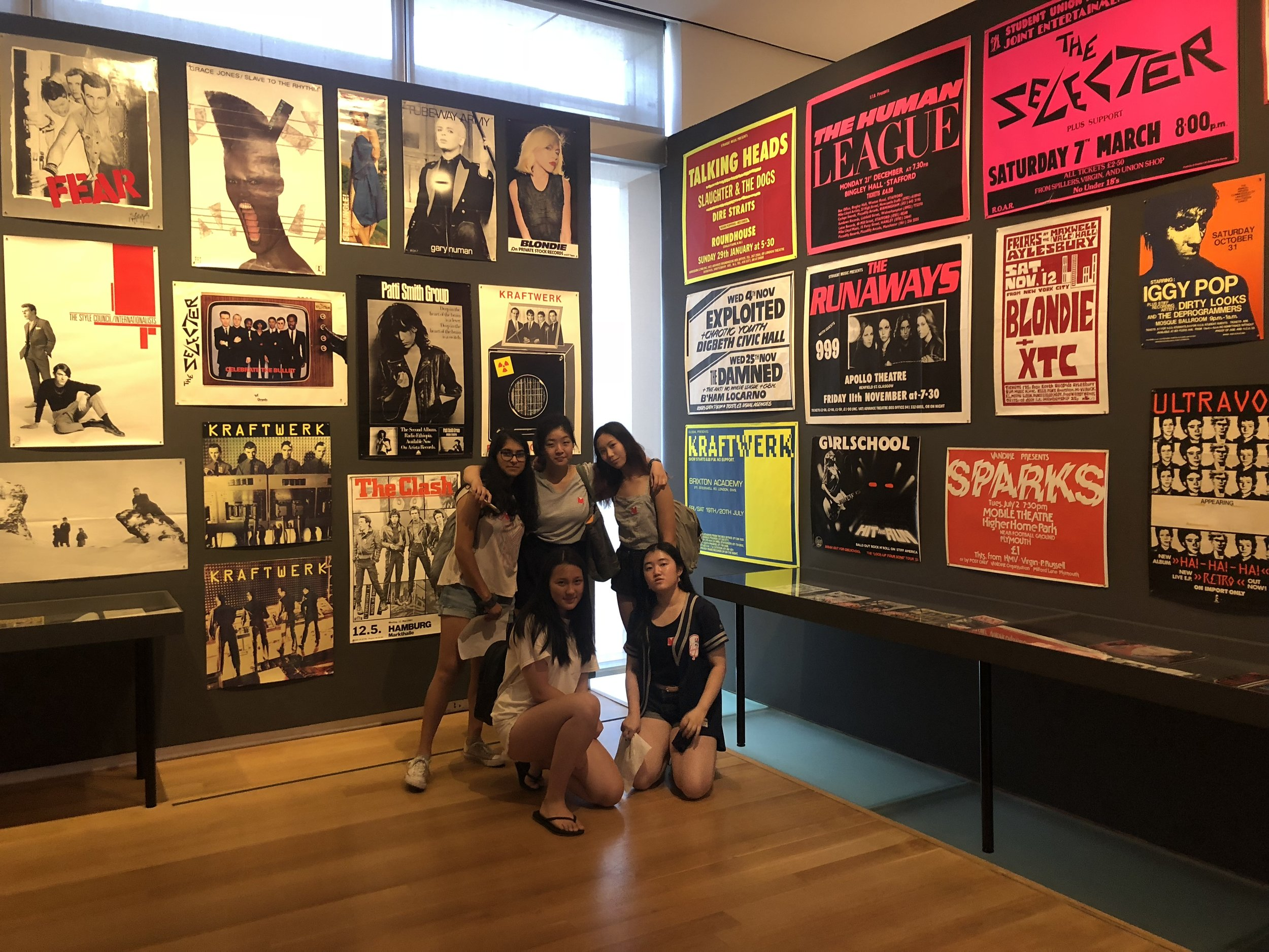 Ria Parikh, Sarah Huang, Amanda Cui, Emily Wang, and Juna Kawai-Yue pose with punk concert posters.