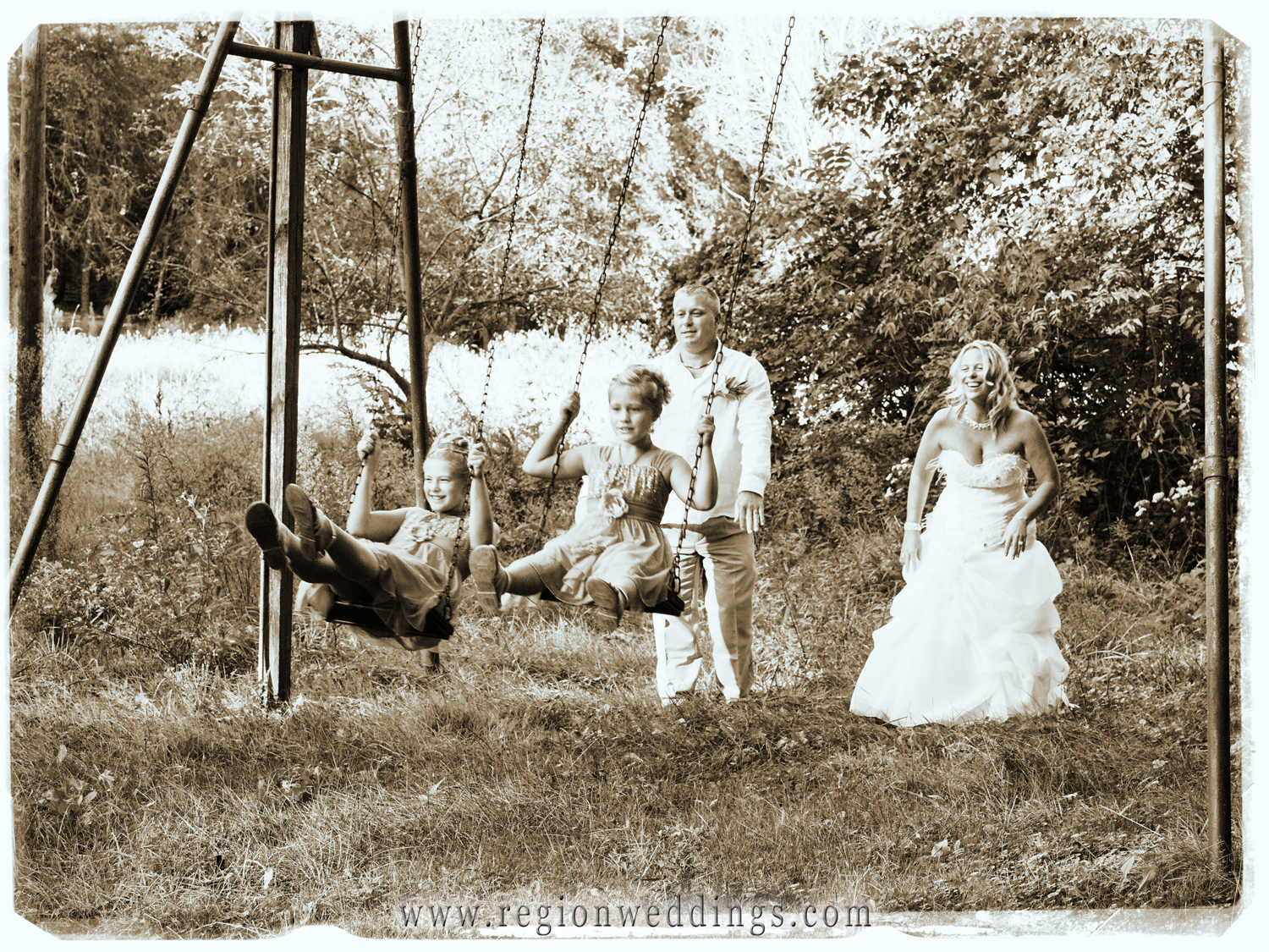 The bride and groom play with their daughters on a swing set before their summer wedding in this tender moment family photo.