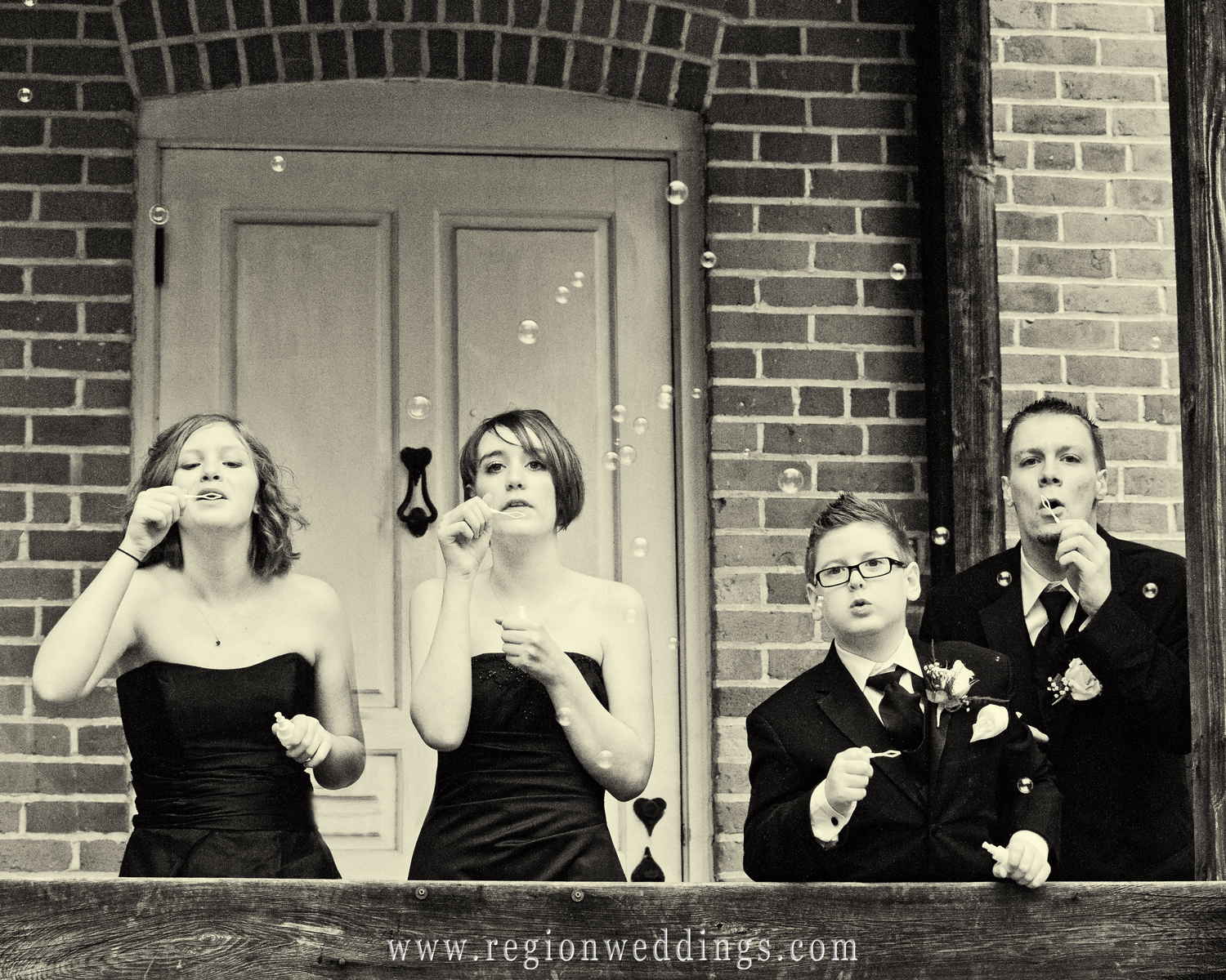 The sons and daughters of the bride and groom blow bubbles at an outdoor wedding at Deep River Park in Hobart, Indiana.