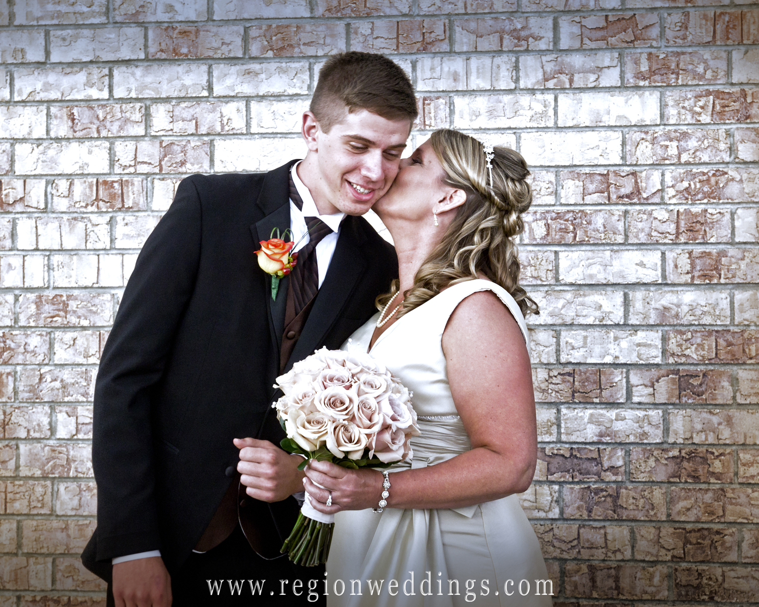 A mom and bride kisses her son as he walks her down the aisle at White Hawk Country Club.