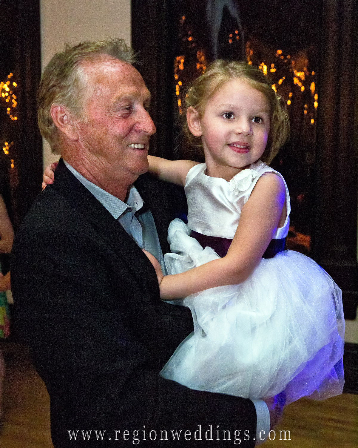 A grandfather dances with the flower girl in this fun, candid wedding photo.