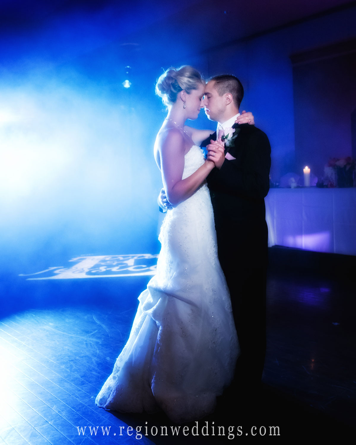 A bride and groom dances their first dance at Avalon Manor in Merrillville as a beautiful blue hue of color engulfs them.