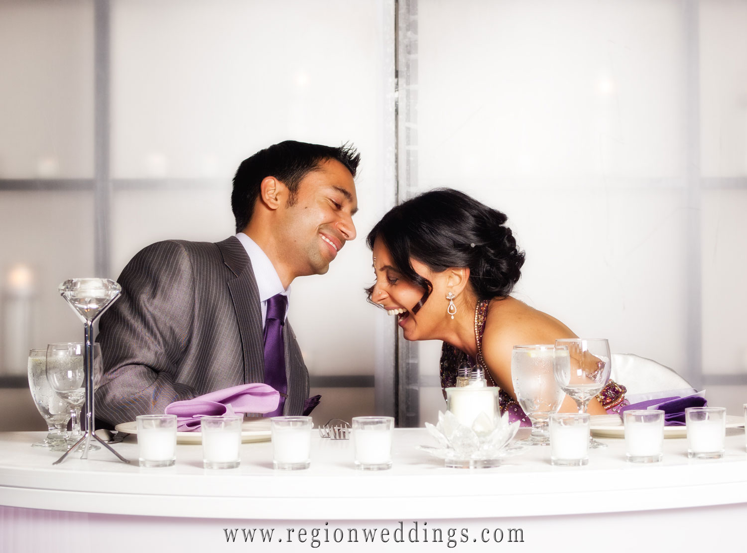 Candid wedding photo of bride and groom laughing at the head table of their wedding reception at the Radisson Hotel in Merrillville.