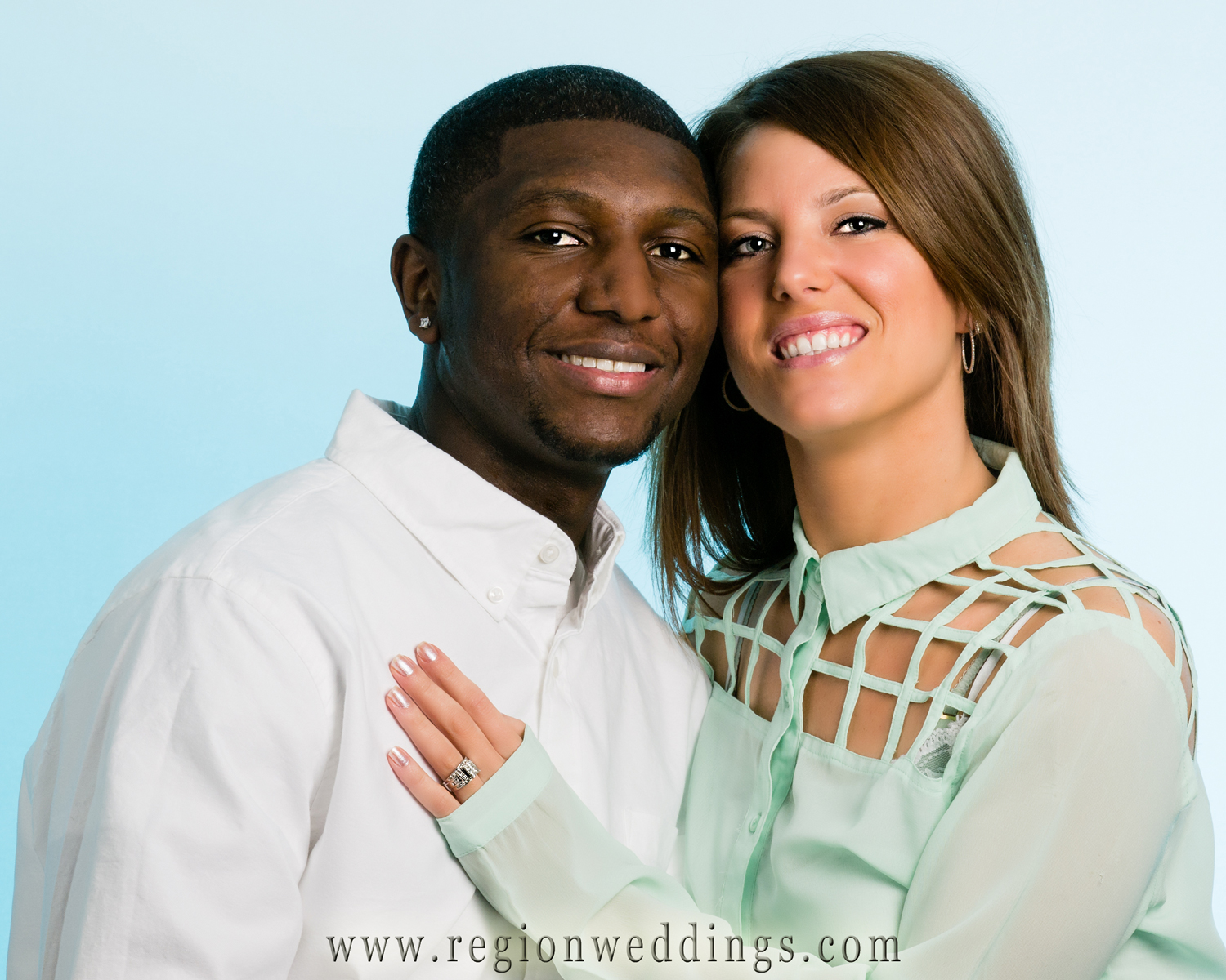 A mixed race couple poses for an engagement photo in a Crown Point portrait studio.