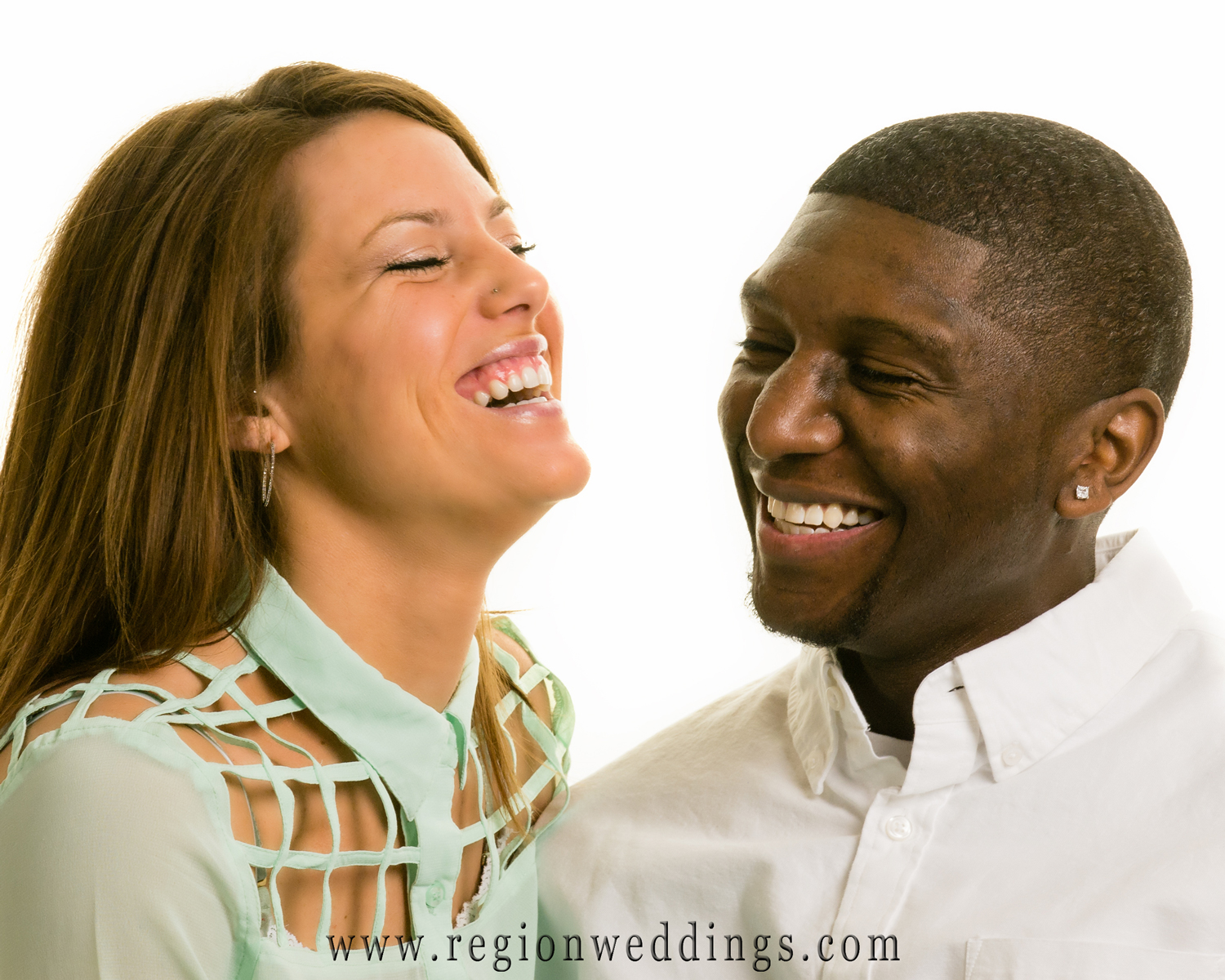 An engaged couple in a natural looking studio portrait laughing and having fun.