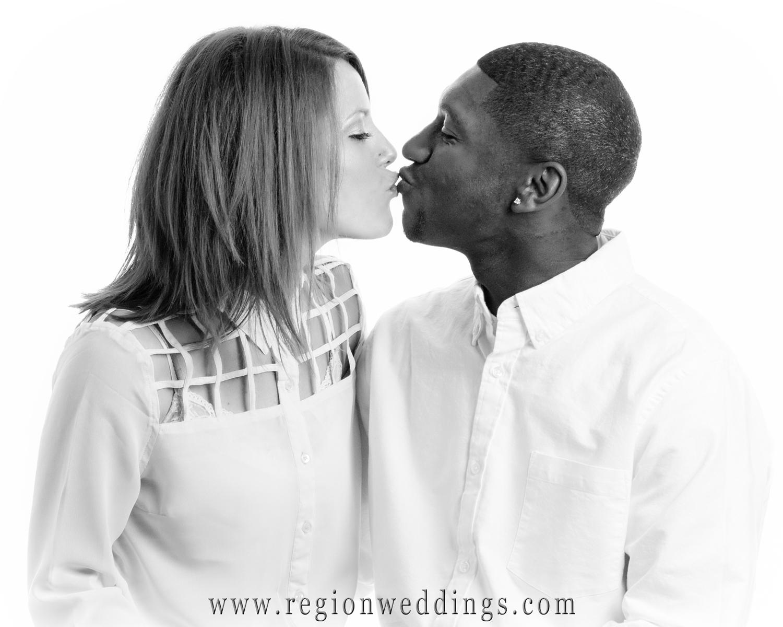An interracial couple kisses for their studio portrait engagement session.