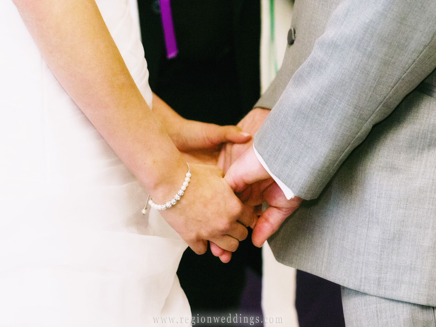 A bride and groom hold hands during their indoor wedding ceremony at The Allure.