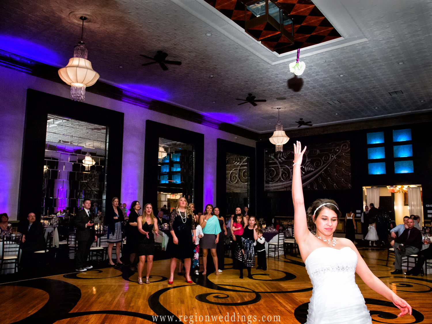 A bride tosses her bouquet at The Allure ballroom in Laporte, Indiana as beautiful purple uplighting fills the room.