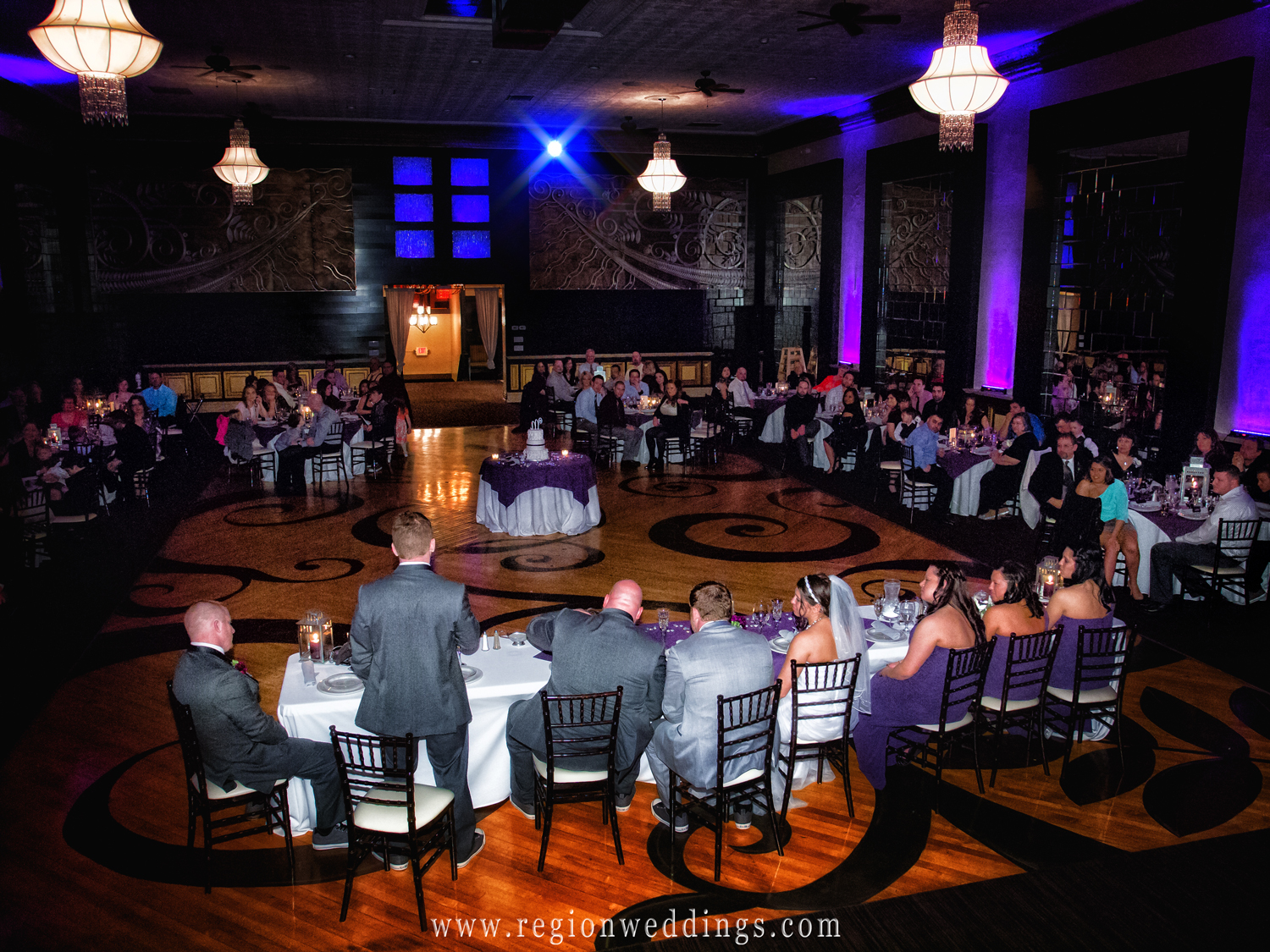 The best man gives his toast as a large group of guests listen and laugh in the spectacular ballroom at The Allure in Laporte, Indiana.