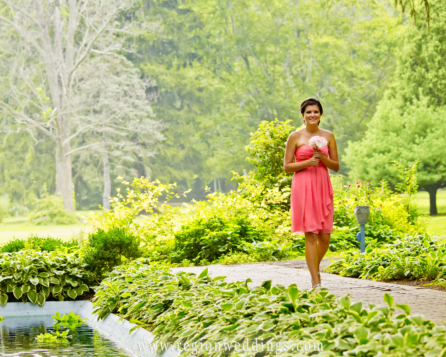A bridesmaid walks along a path with a waterfall and gorgeous greenery in the background for an outdoor wedding at International Friendship Garden.