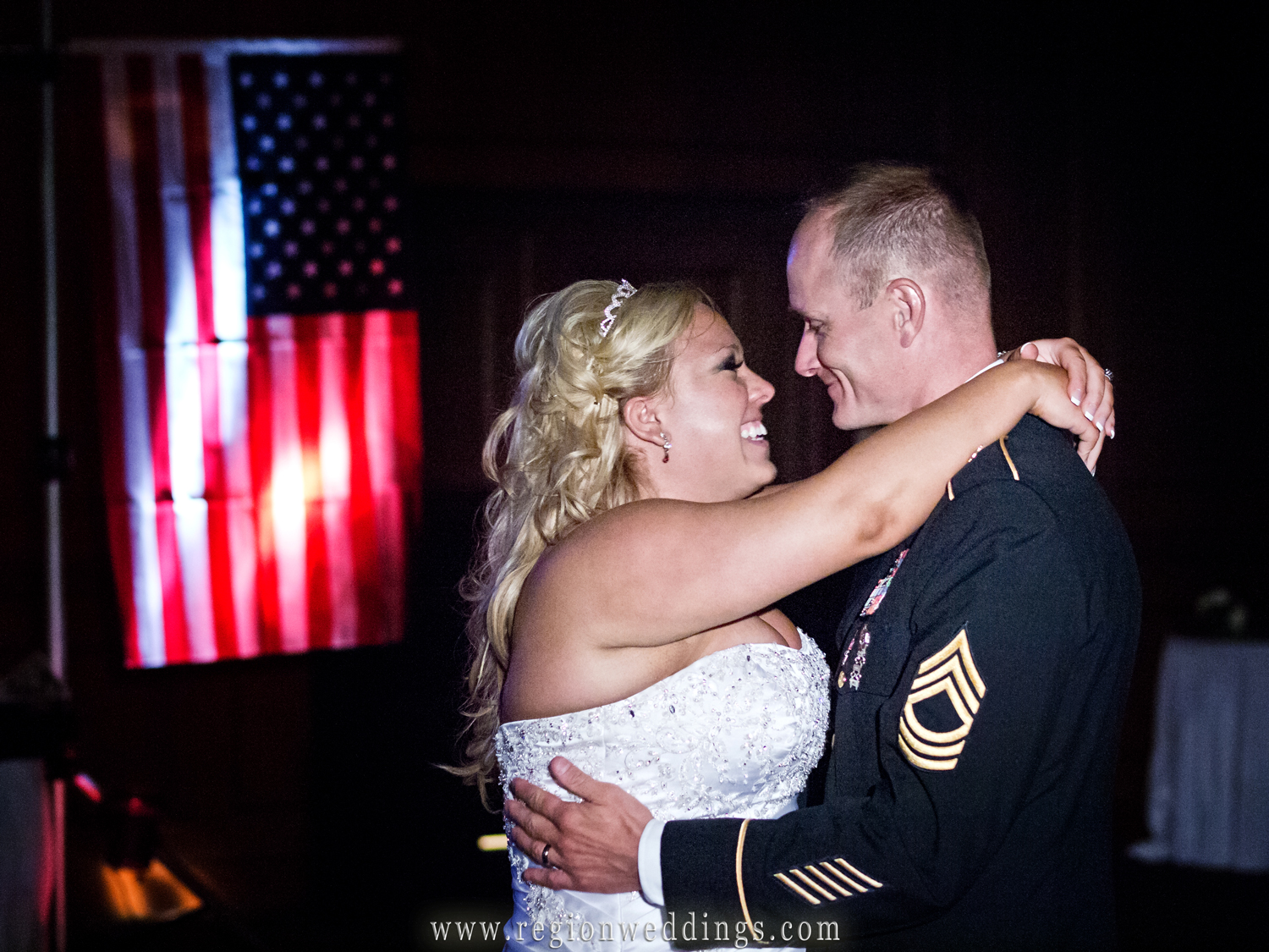 A military bride and groom dance in front of the American flag at Wicker Park Social Center.