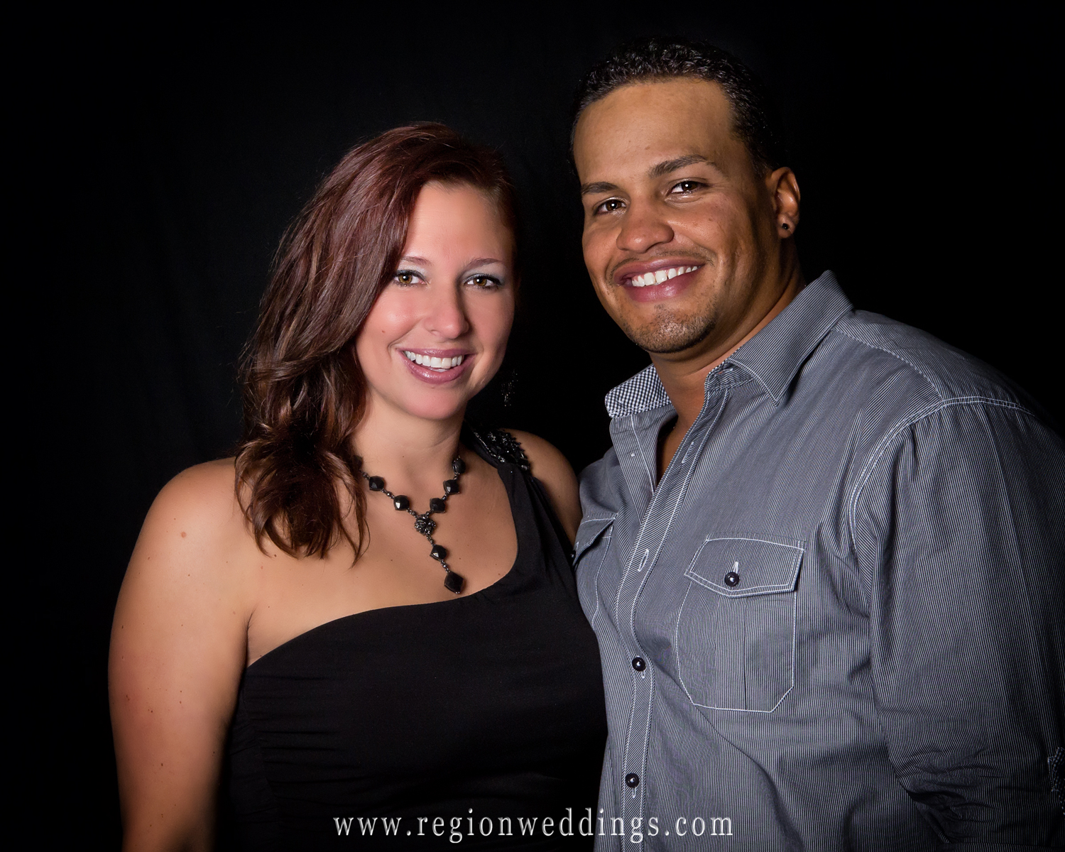 A couple poses for studio style portraits at their friend's wedding reception at Cloister in the Woods.