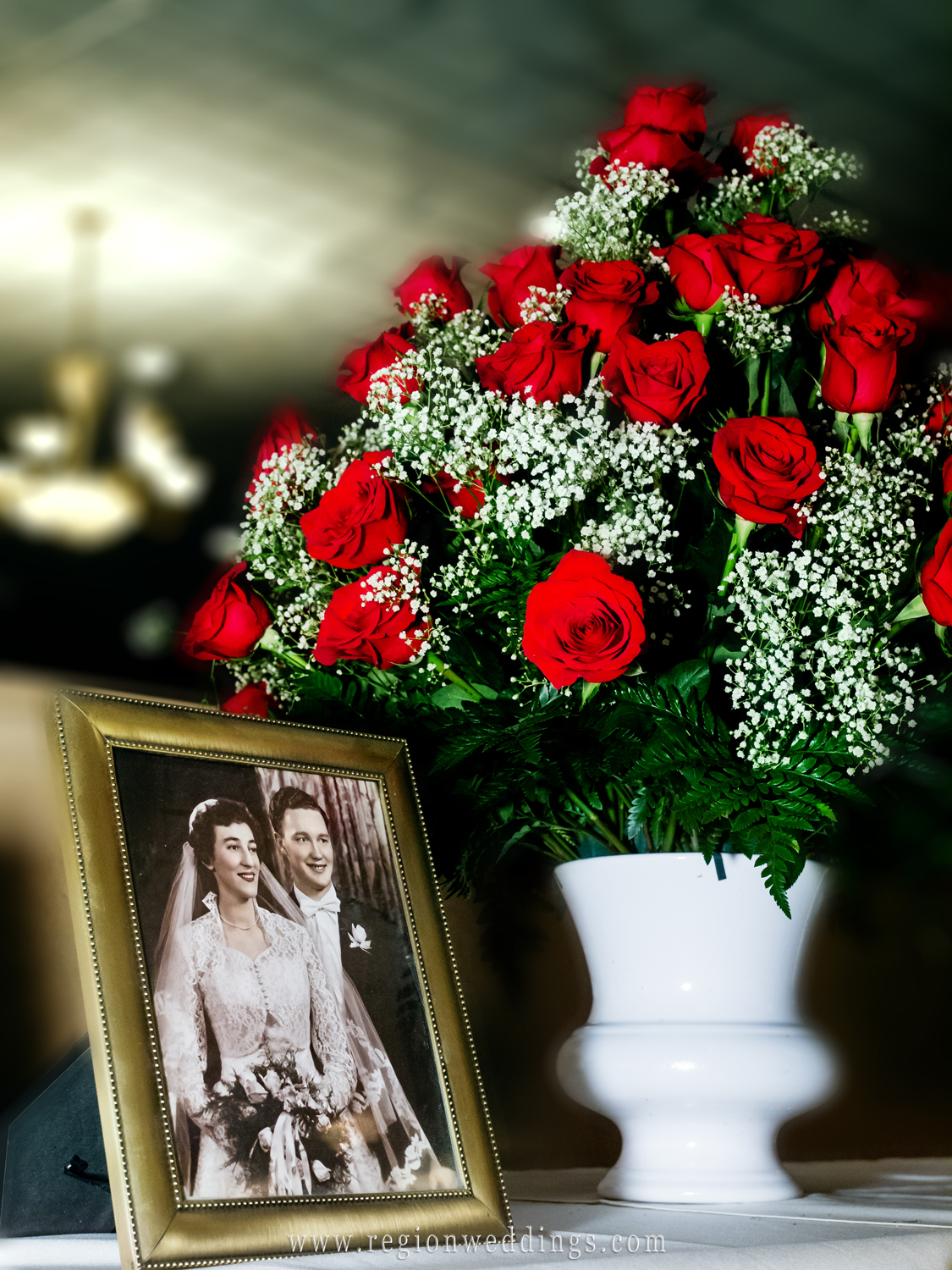 A vintage wedding photo sits next to 60 red roses at an Anniversary Party at Andorra Banquet Hall.