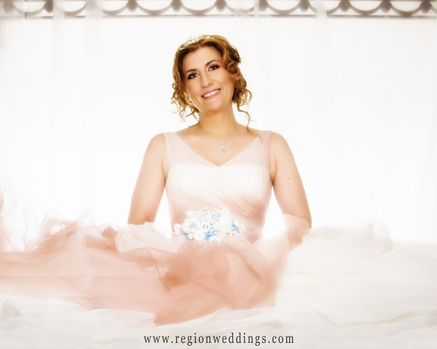 Bride poses on the top of her bed for an artistic wedding photo at her home in Schererville, Indiana.